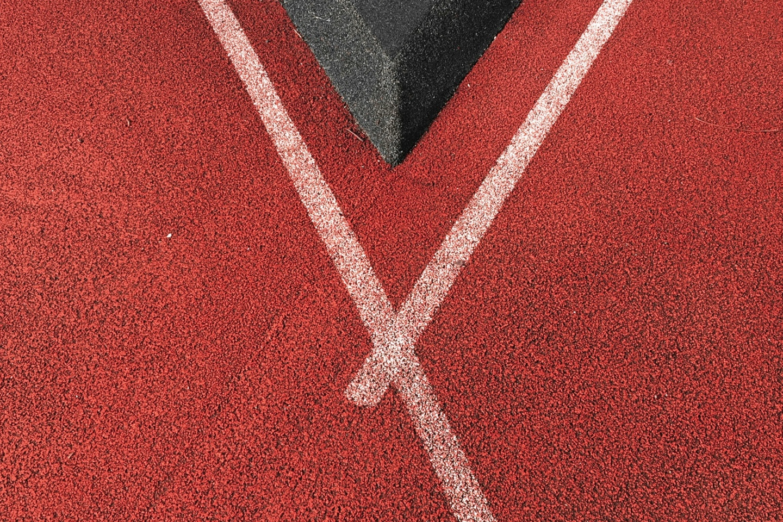 Fitnessblogs: Tartanbahn mit weißer Linie trifft auf eine graue Kante