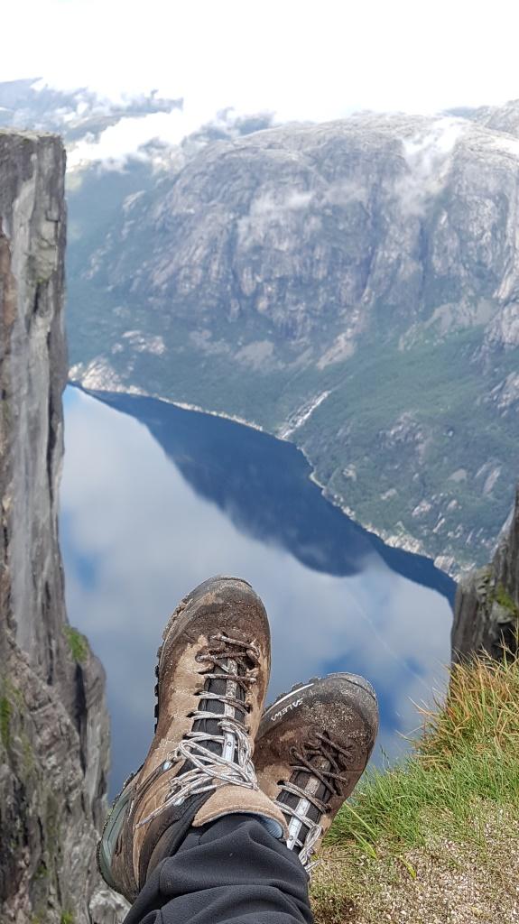 Hinter den Wanderschuhen eröffnet sich die Aussicht vom Kjeragbolten auf den Fjord