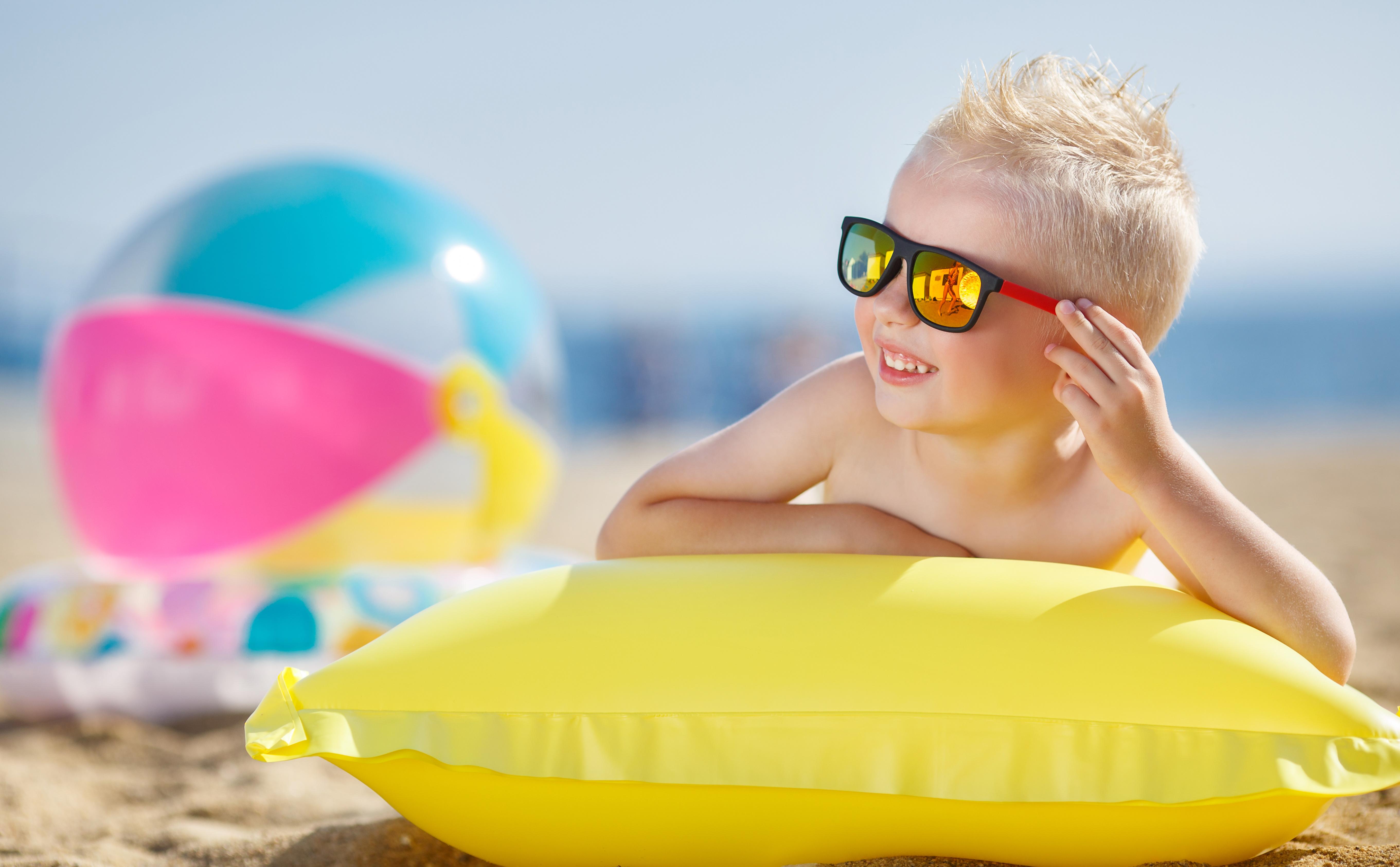 Krank im Urlaub: Ein kleiner Junge mit blonden kurzen Haaren trägt eine Sonnenbrille und liegt einer Luftmatratze lächelnd am Strand