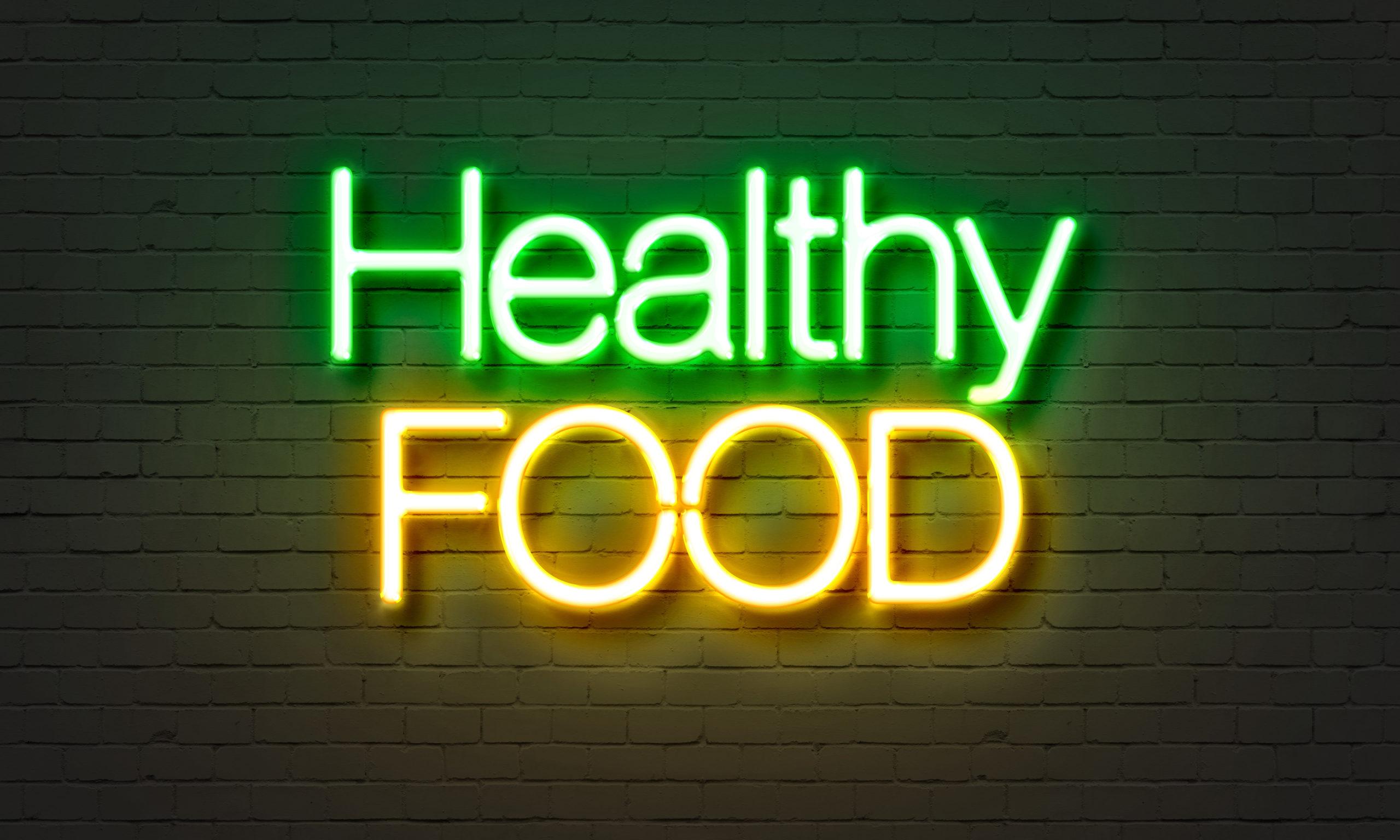 Clean Eating: Neonschild mit Aufschrift Healthy food auf einer Ziegelsteinwand