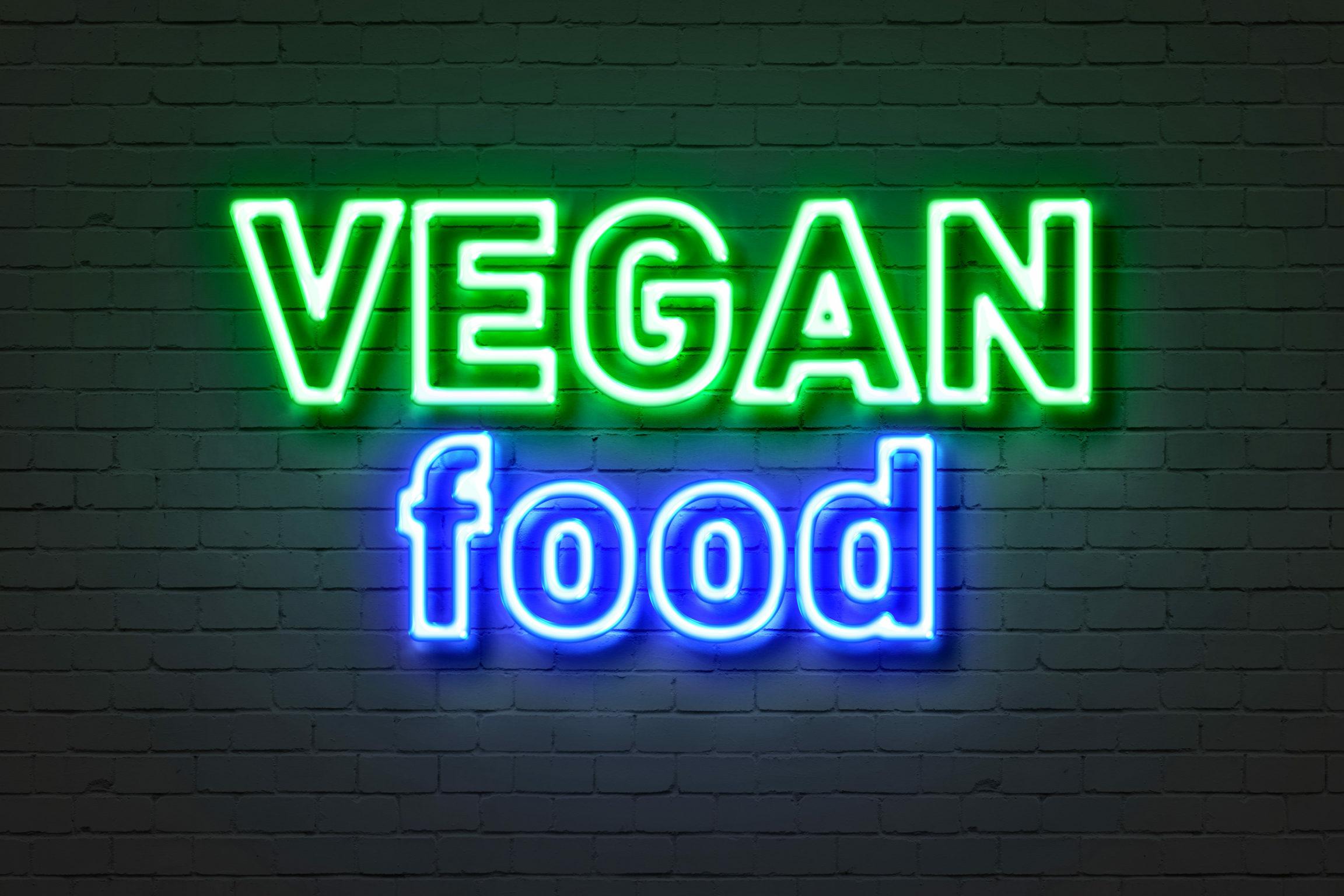 Vegan: Neonschild mit Aufschrift Vegan food auf einer Ziegelsteinwand