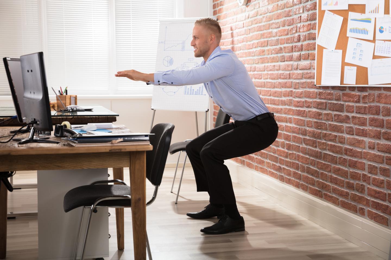 Bürosport Challenge: Ein Mann im Anzug macht hinter seinem Schreibtisch Kniebeugen