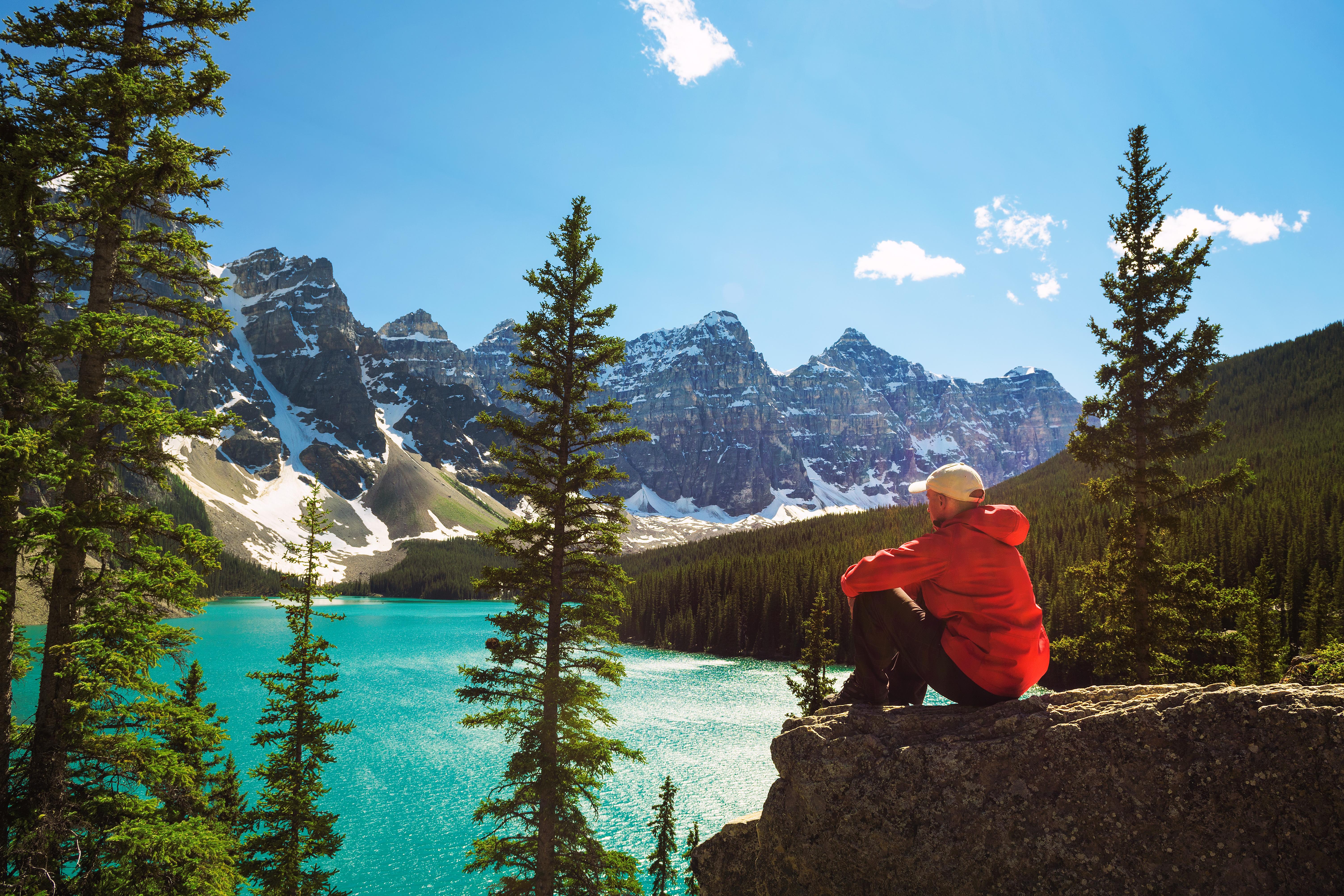 Mindfulness: In Mann in roter Jacke sitzt auf einem Stein und blickt auf den Morraine Lake