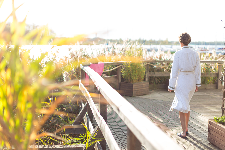 Lieblingssauna: Frau auf der Terrasse einer Sauna am See