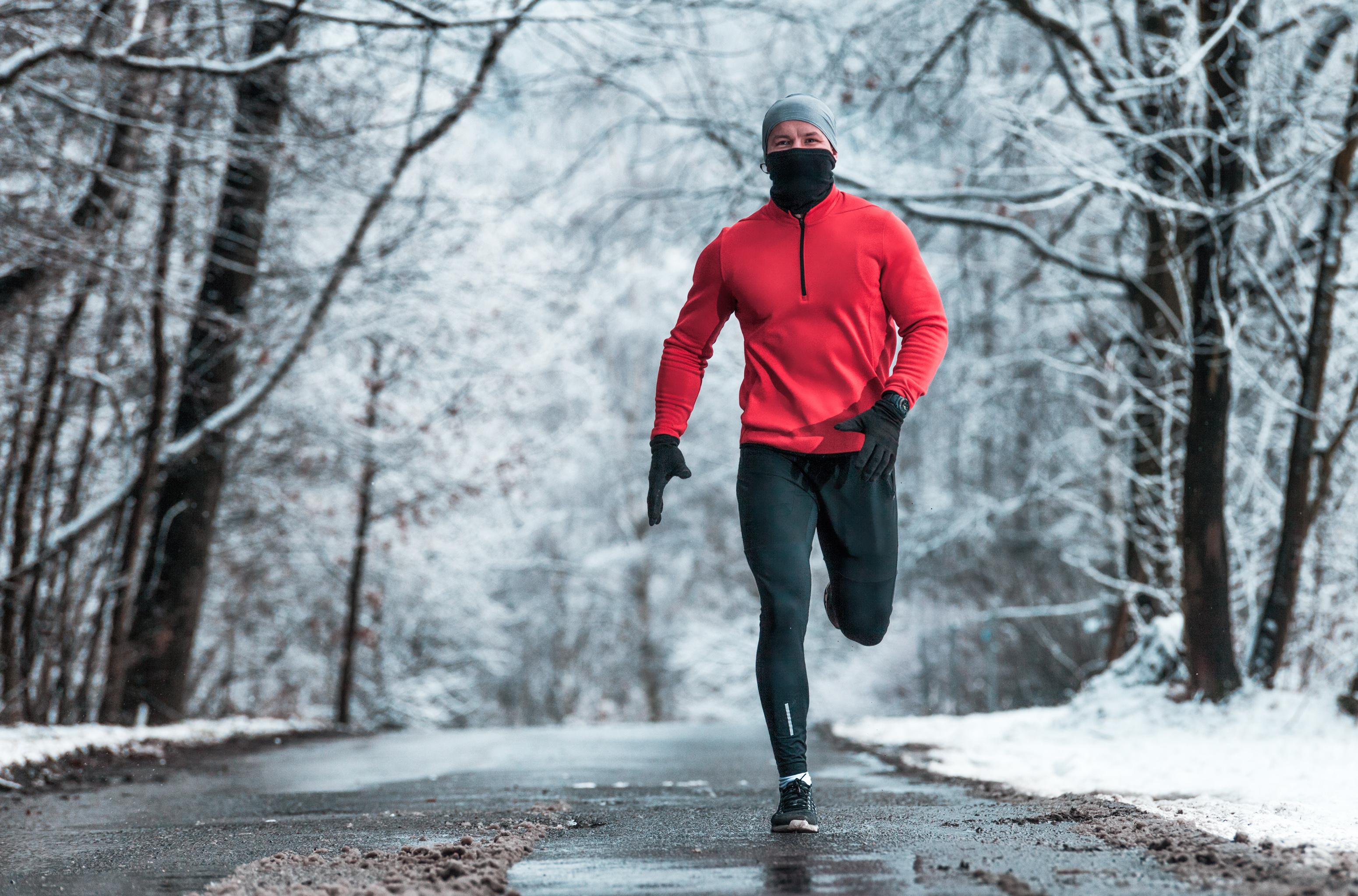 Laufen im Winter: Mann mit Mütze, Schal und Handshuh joggt durch Winterlandschaft