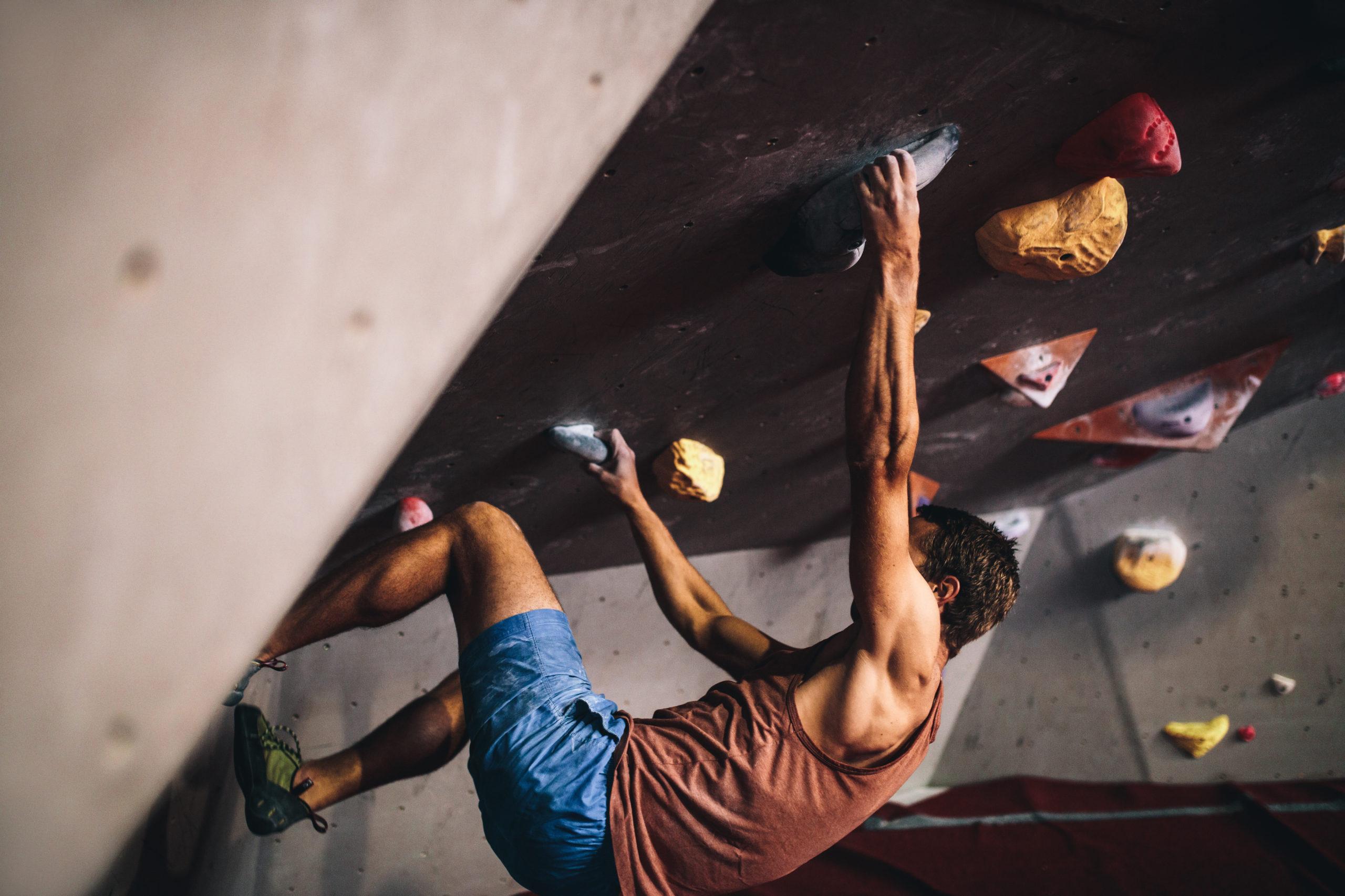 Bouldern: Ein Mann klettert in der Indoor-Halle