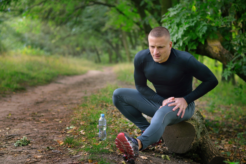 Laktatdiagnostik: Junger Mann im Jogging-Outfit sitzt auf einem Baumstamm im Park und hält seinen schmerzenden Oberschenkel