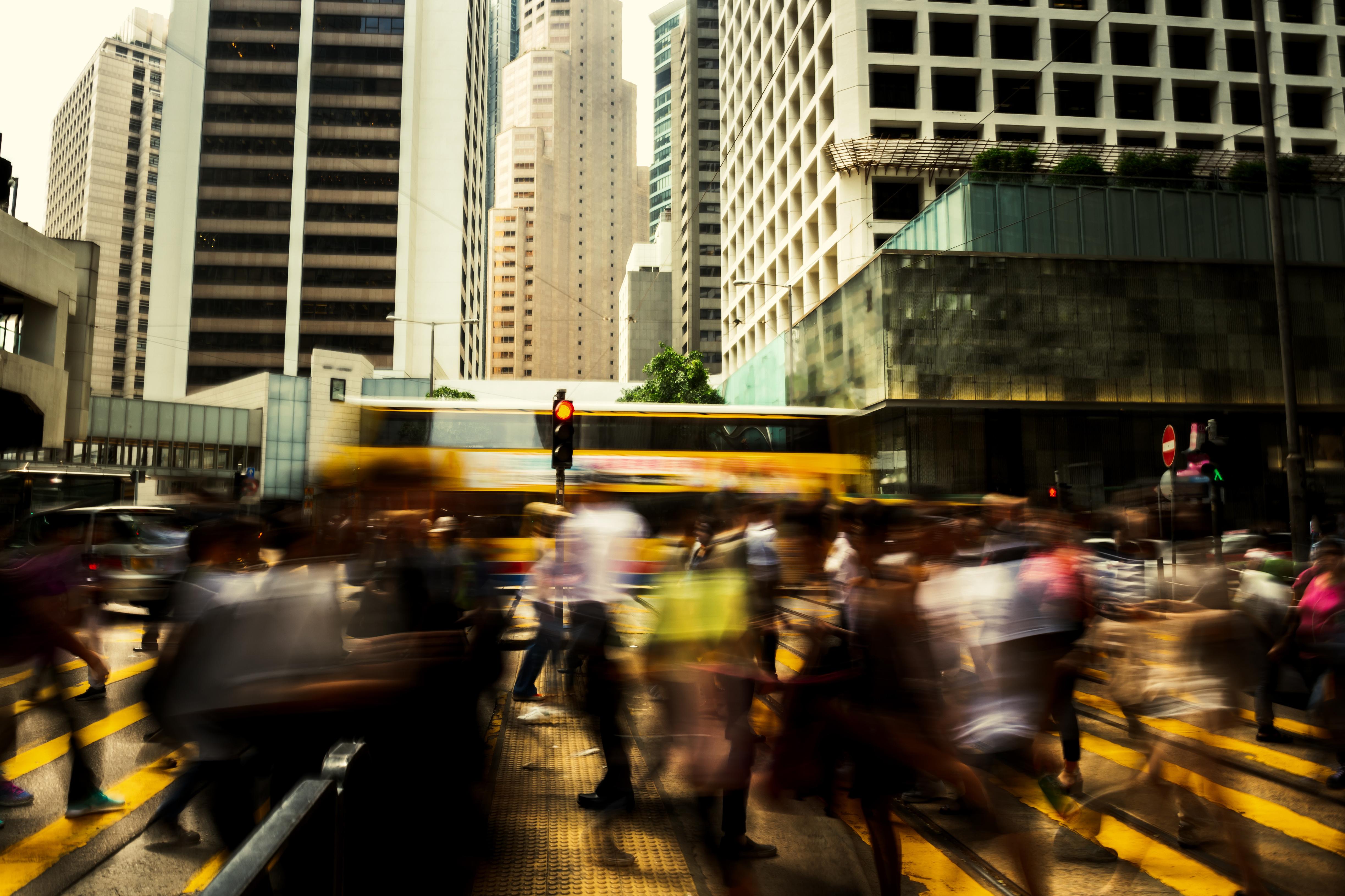 Lärm: Straßenkreuzung in Großstadt mit viel Verkehr und vielen Fußgängern