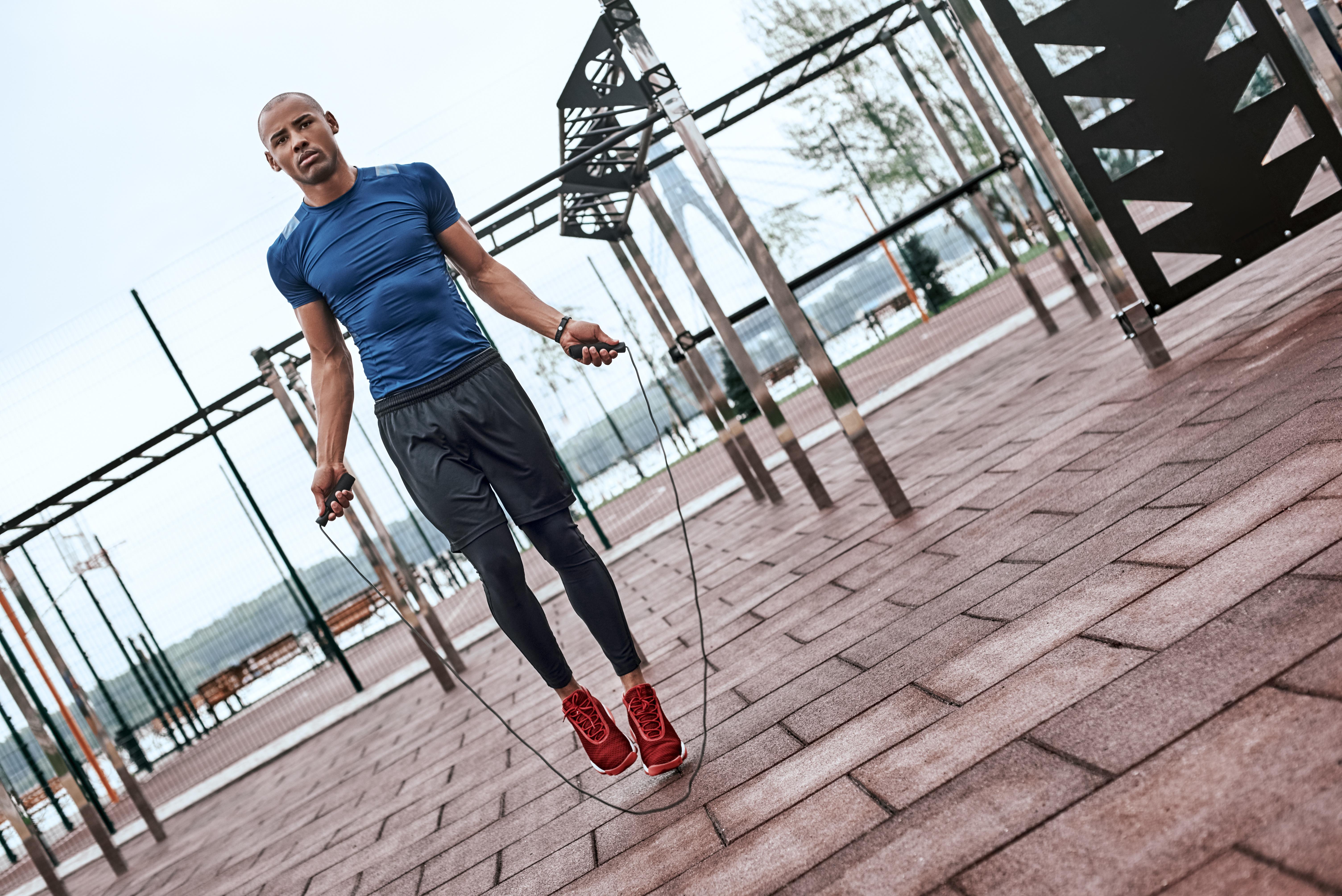 Seilspringen: Ein Mann springt draußen auf einem Trainingsparcours Seil