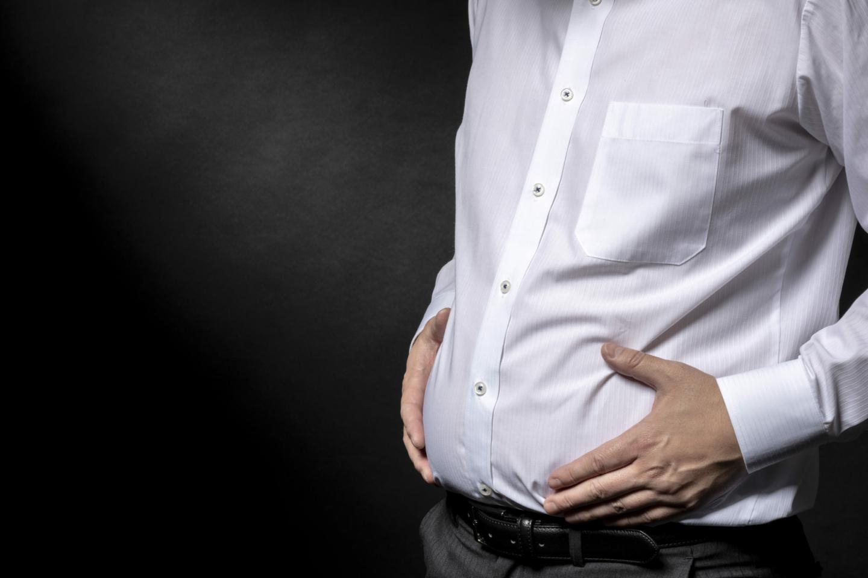 DadBod: Ein Mann im weißen Hemd umfasst mit den Händen seinen kleinen Bauch