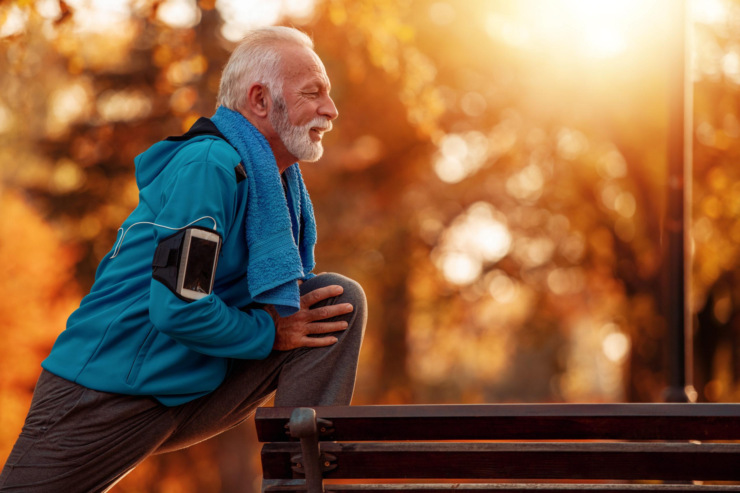 Training fürs Immunsystem: Ein älterer Herr bei Stretching-Übungen im Park während des Herbst