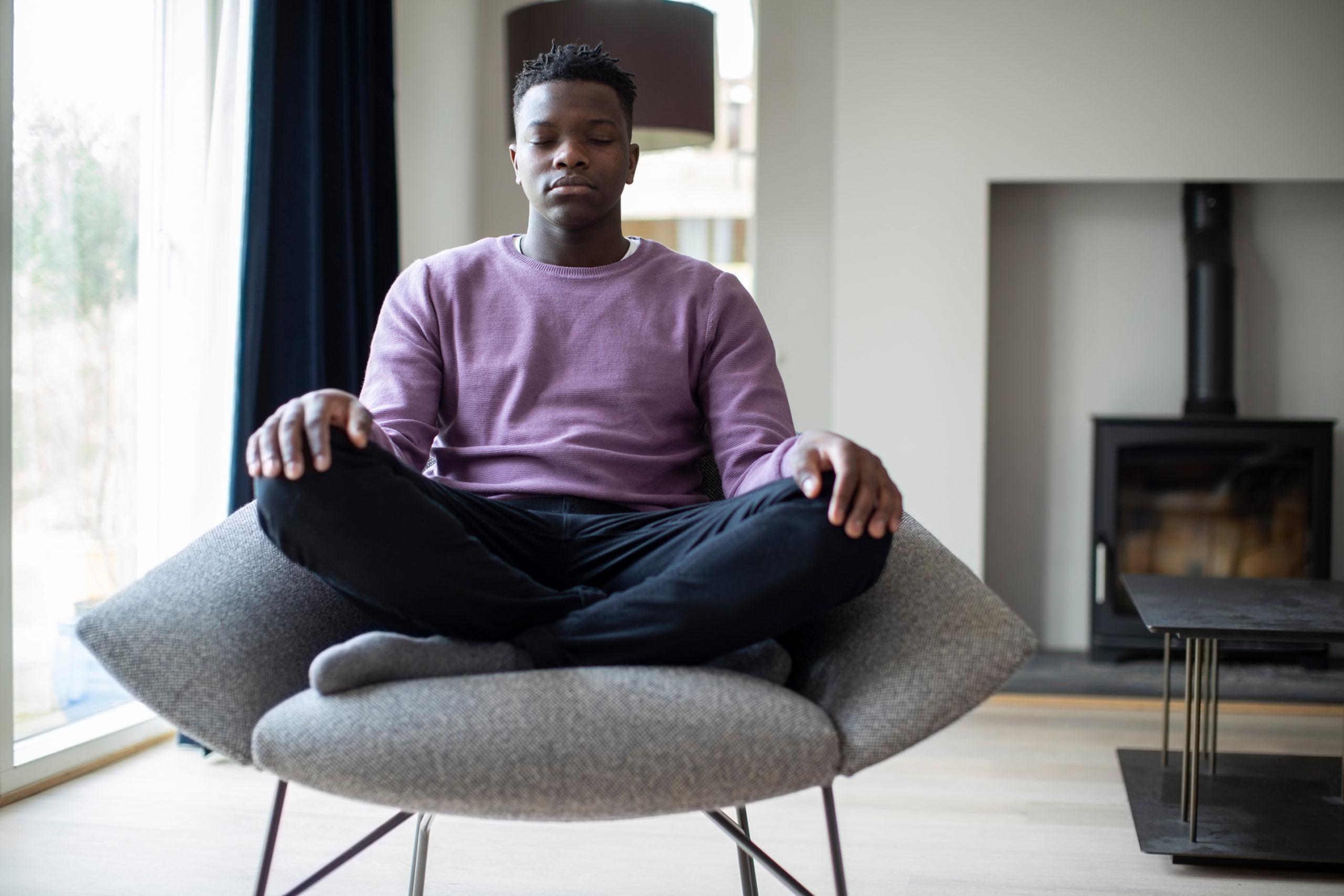 Meditation: Ein junger Mann sitzt im auf einem Sessel im Wohnzimmer und meditiert