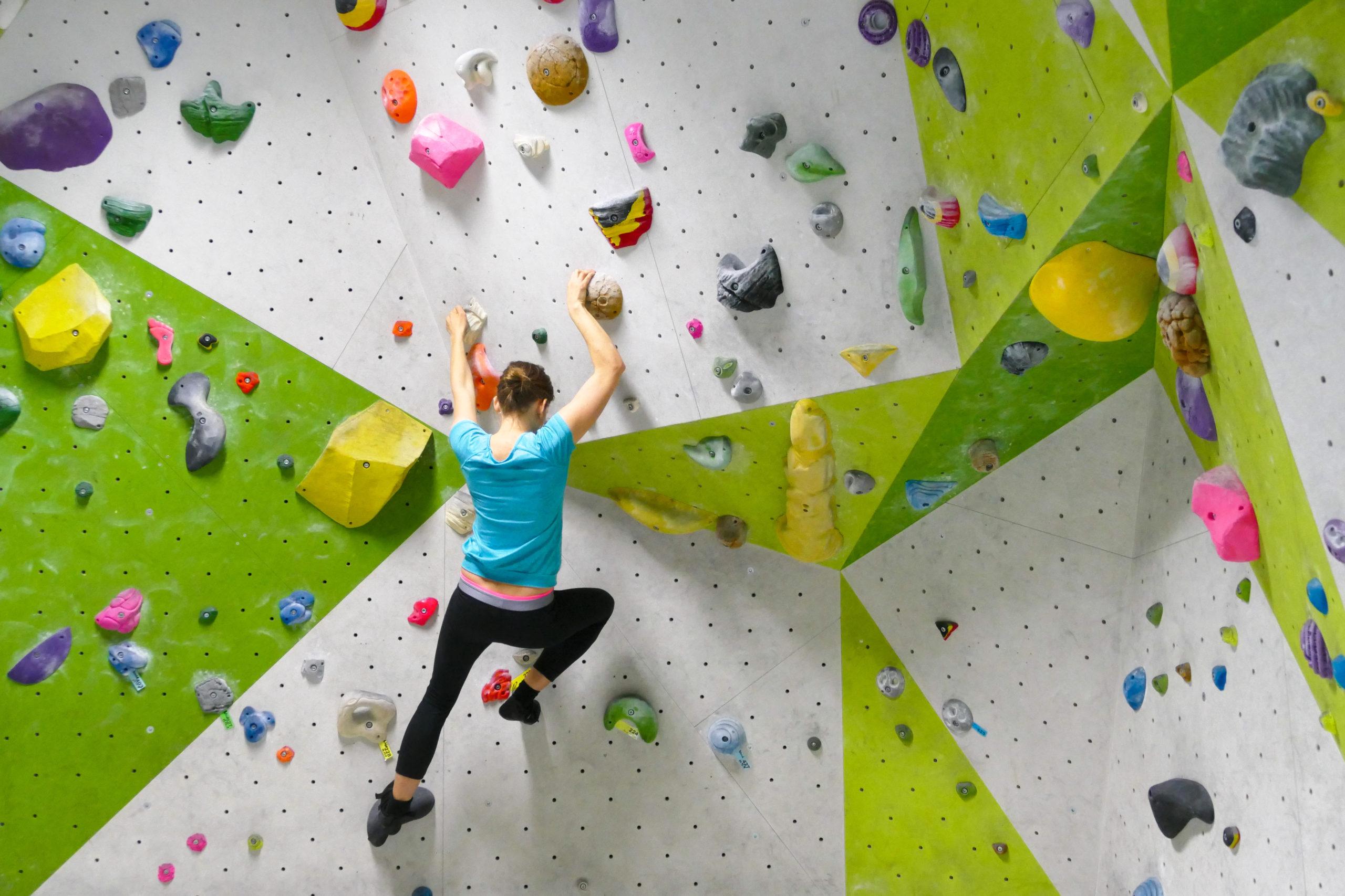 Junge Frau boulderd in Kletterhalle