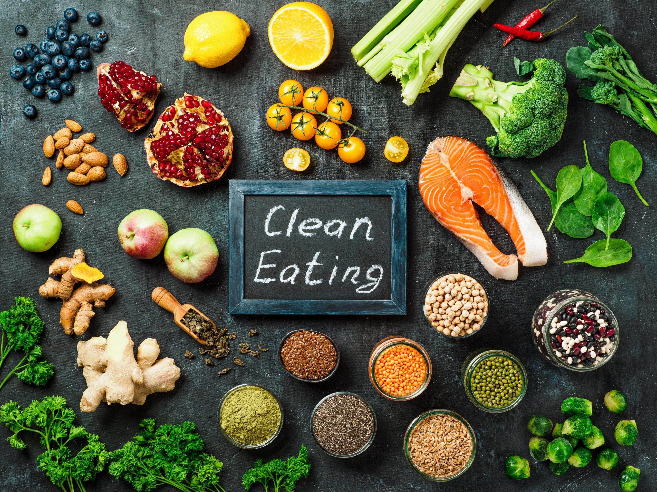 Konzept Clean Eating: Auswahl an Speisen und Zutaten umringen eine Tafel auf der mit Kreide Clean Eating steht