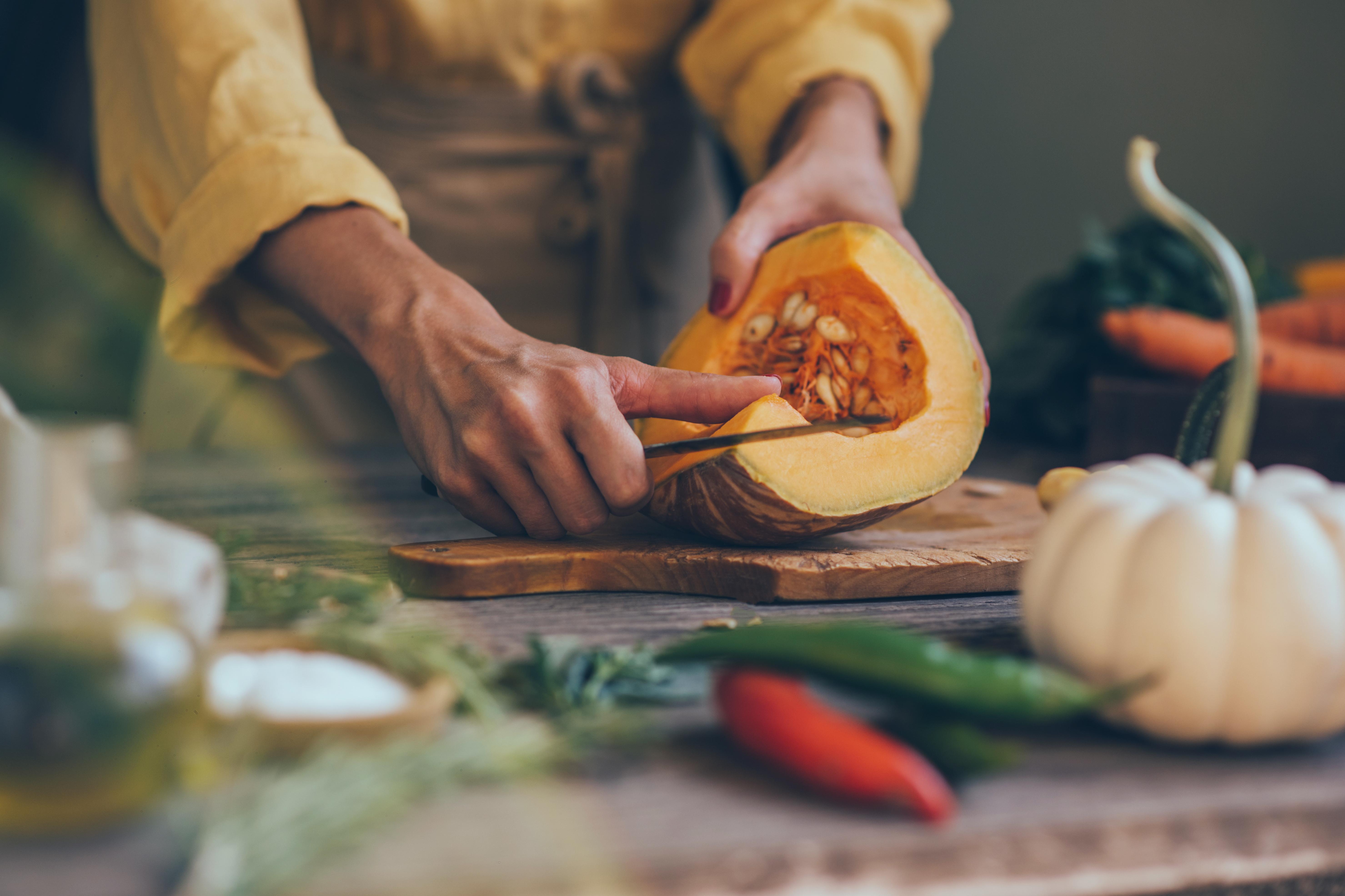 Frau schneidet Kürbis auf dunklem Küchentisch mit Gemüse