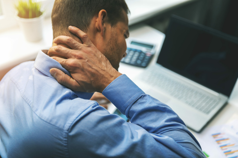 Sitzen: Ein Mann sitzt am Schreibtisch und massiert den Nacken während er am Computer arbeitet