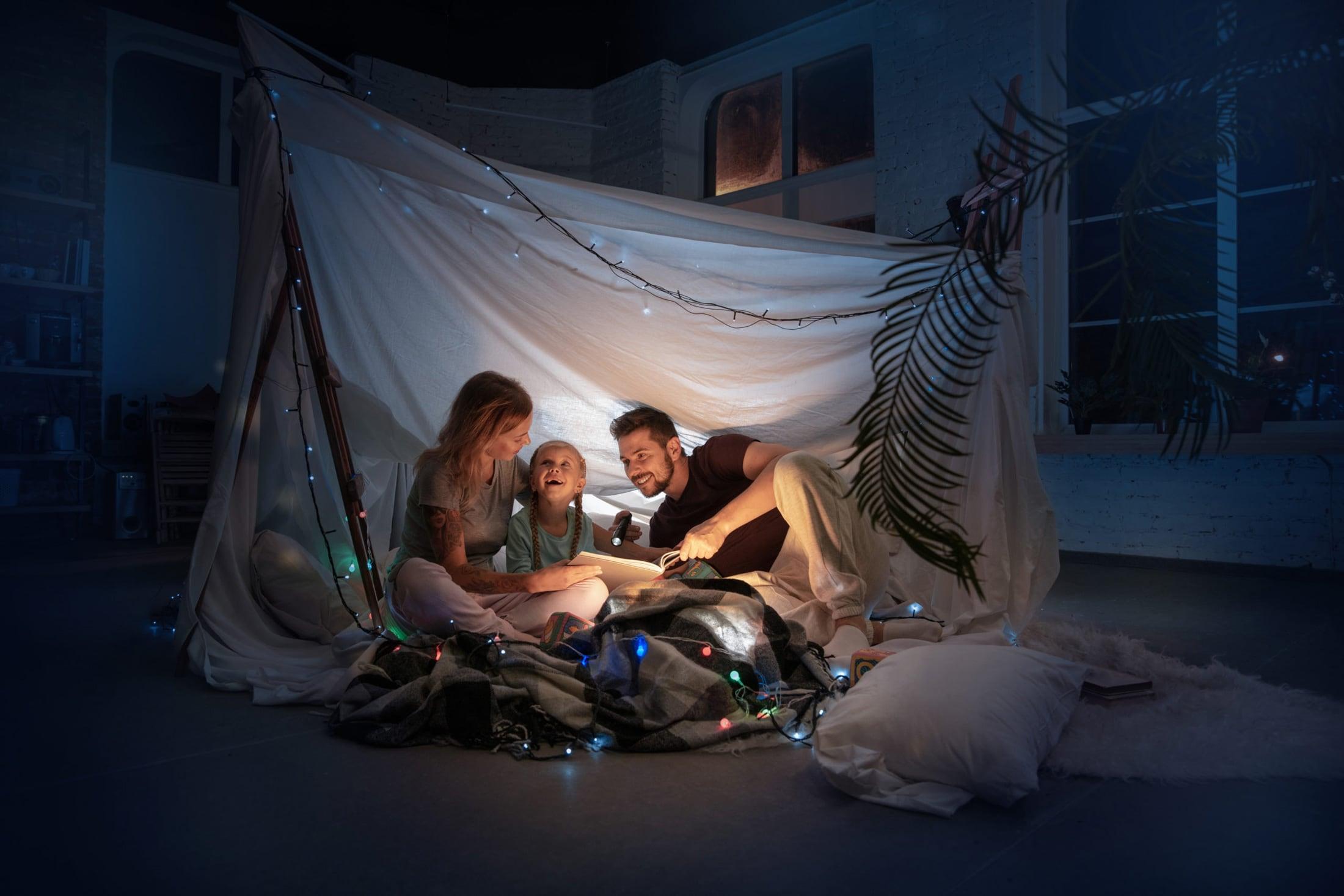 Familie sitzt in einem dunklen Raum in einem selbstgebauten Zelt und ließt mit einer Taschenlampe ein Buch.