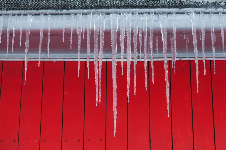 Schmilzende Eiszapfen vor roter Holzwand