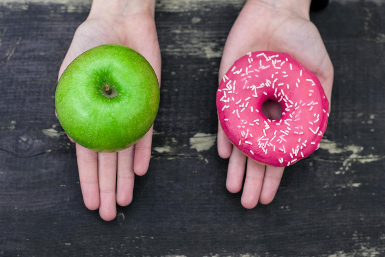 Zucker: Zwei Hände nebeneinander mit einem Apfel in der einen und einem Donut in der anderen Hand