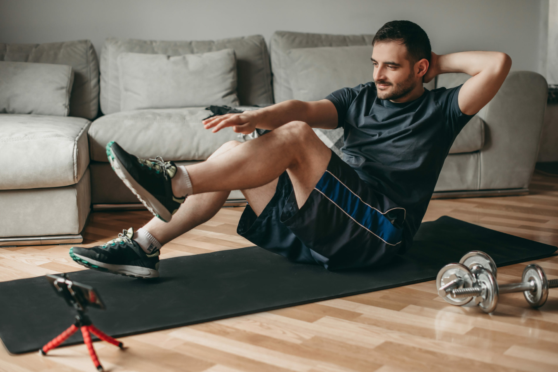 Junger Mann schaut sich Sportügungen auf einem Smartphone an und führt diesw auf einer Matte aus.