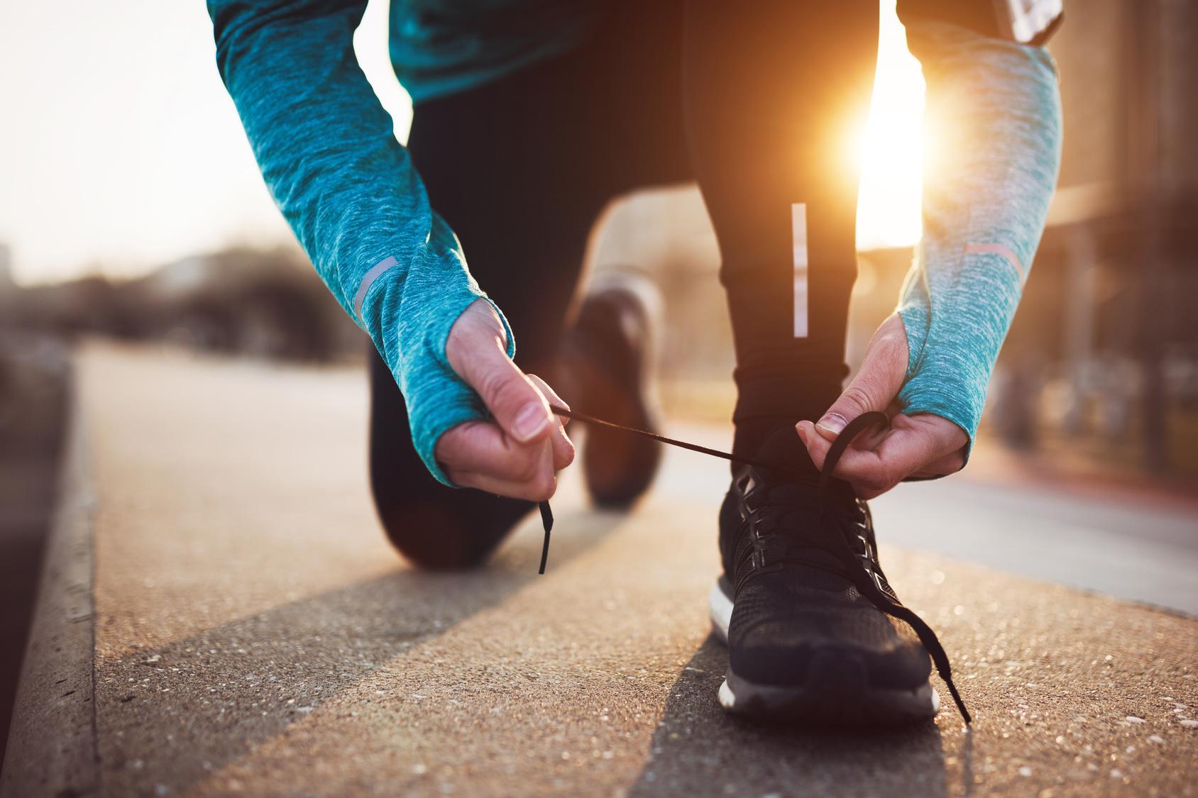 Läufer bindet sich auf einer Straße eine Schuh zu.