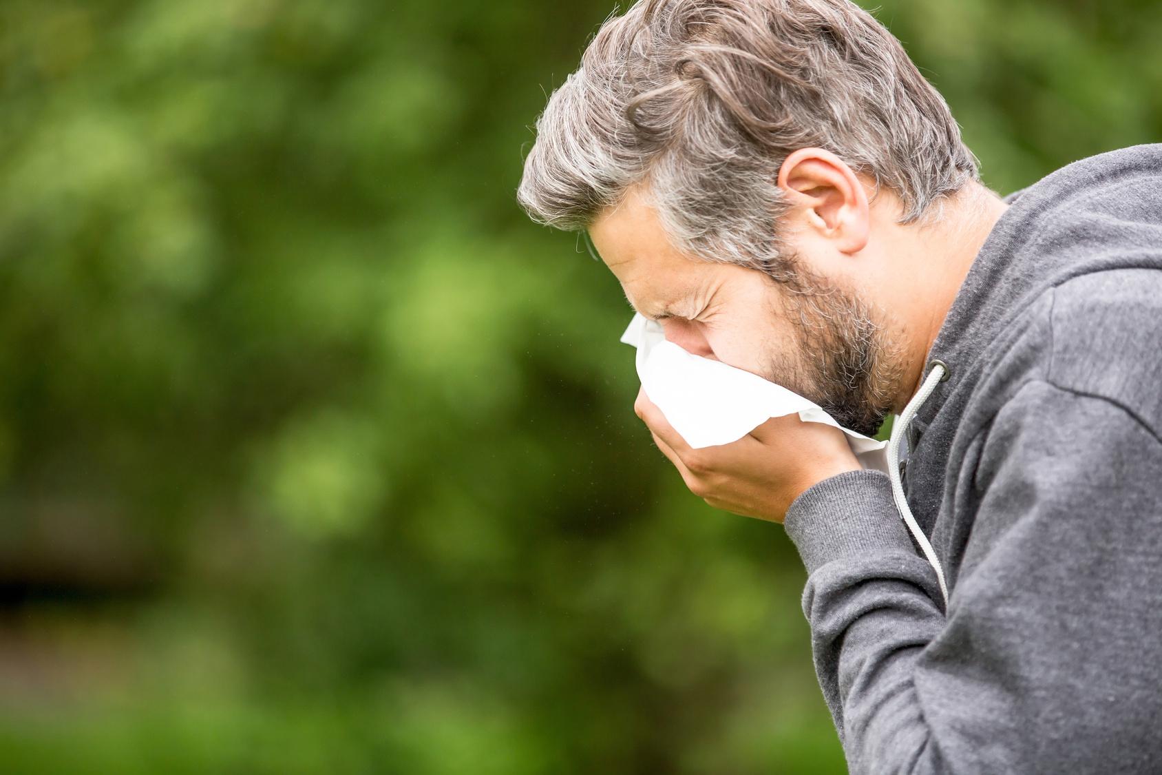 Mann mit Allergie und Heuschnupfen beim Niesen in ein Taschentuch