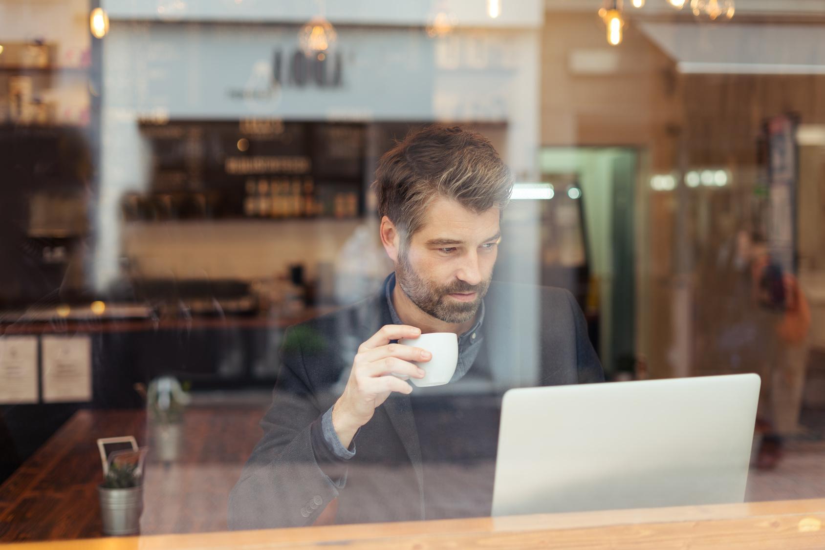 Work-Life-Balance: Ein Mann sitzt hinter einem Café-Fenster und arbeitet am Laptop. Er trinkt dabei Kaffee. Darstellung Work-Life-Balance