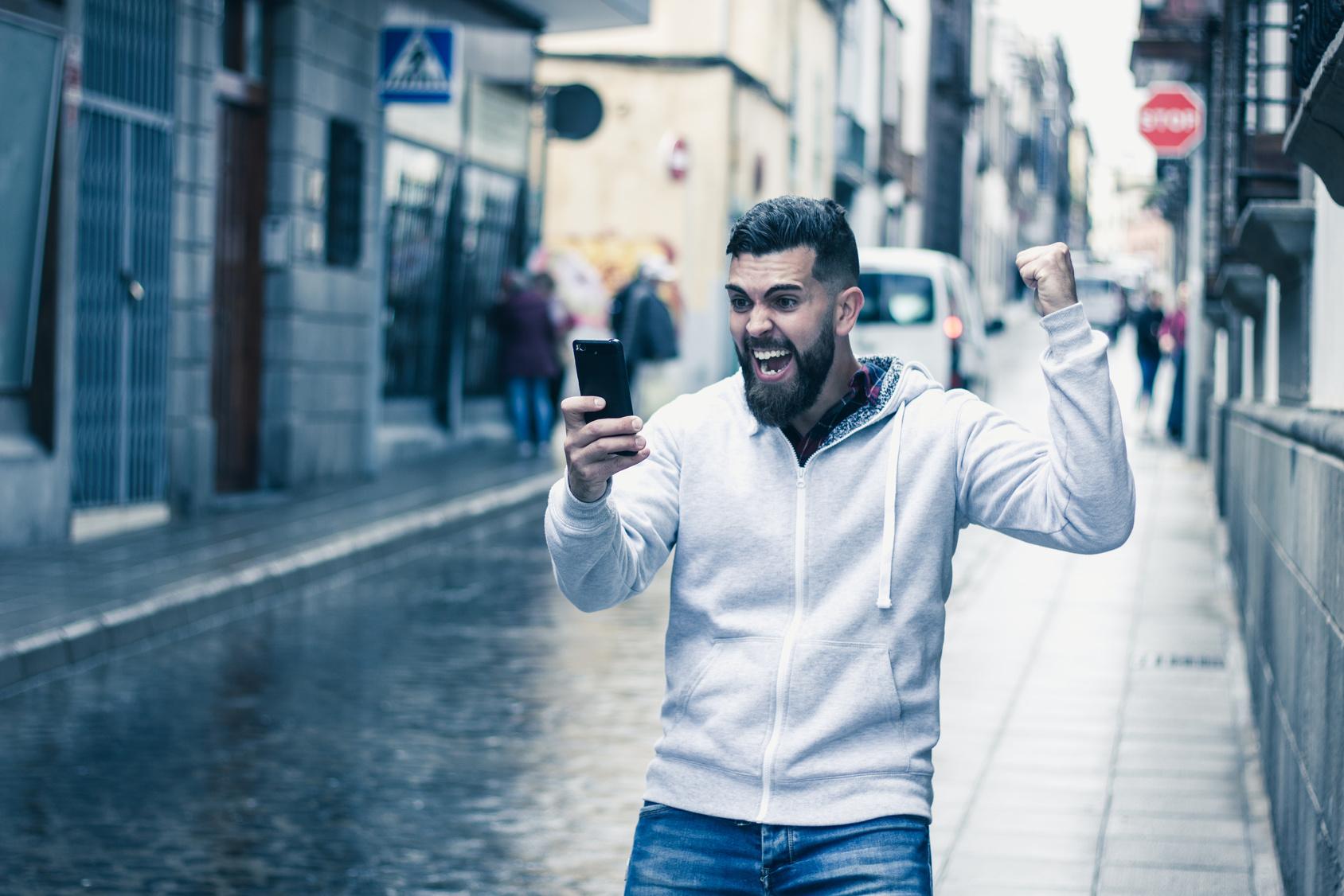 WM-Apps für den Fußball-Sommer: Junger Mann mit Bart schaut auf der Straße auf sein Smartphone und jubelt.
