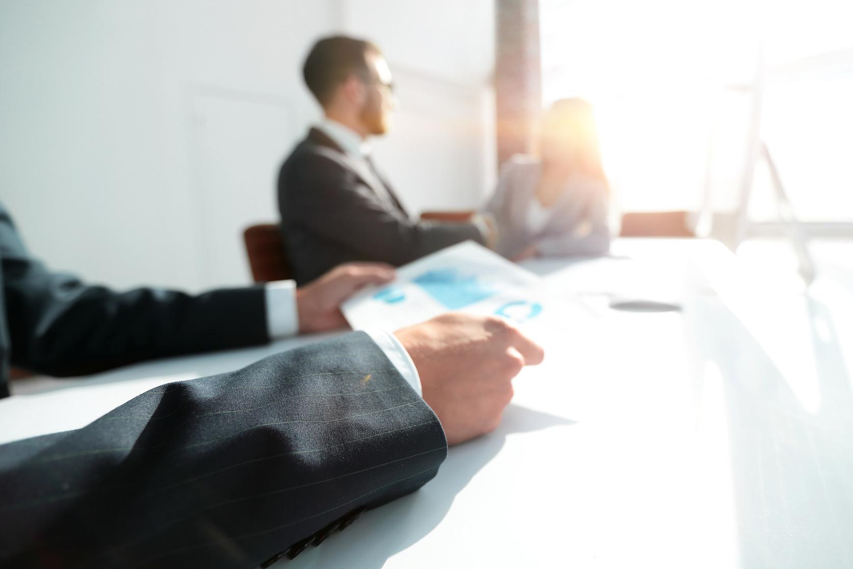 Zwei Männer sitzen im gegenlicht in einem Büro.