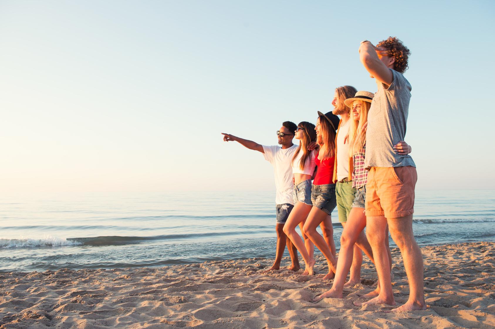 Hauttyp: 6 junge Menschen stehen am Strand und schauen in die Sonne