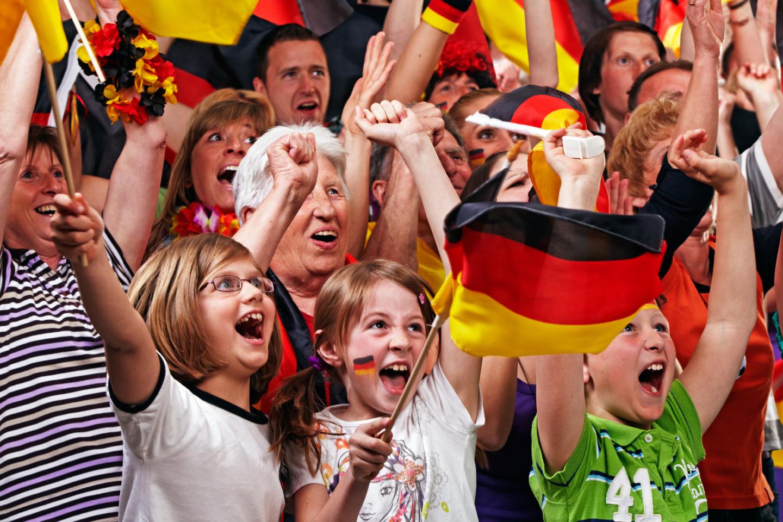 Kinder und Erwachsene jubeln in der Gruppe als Fußballfans