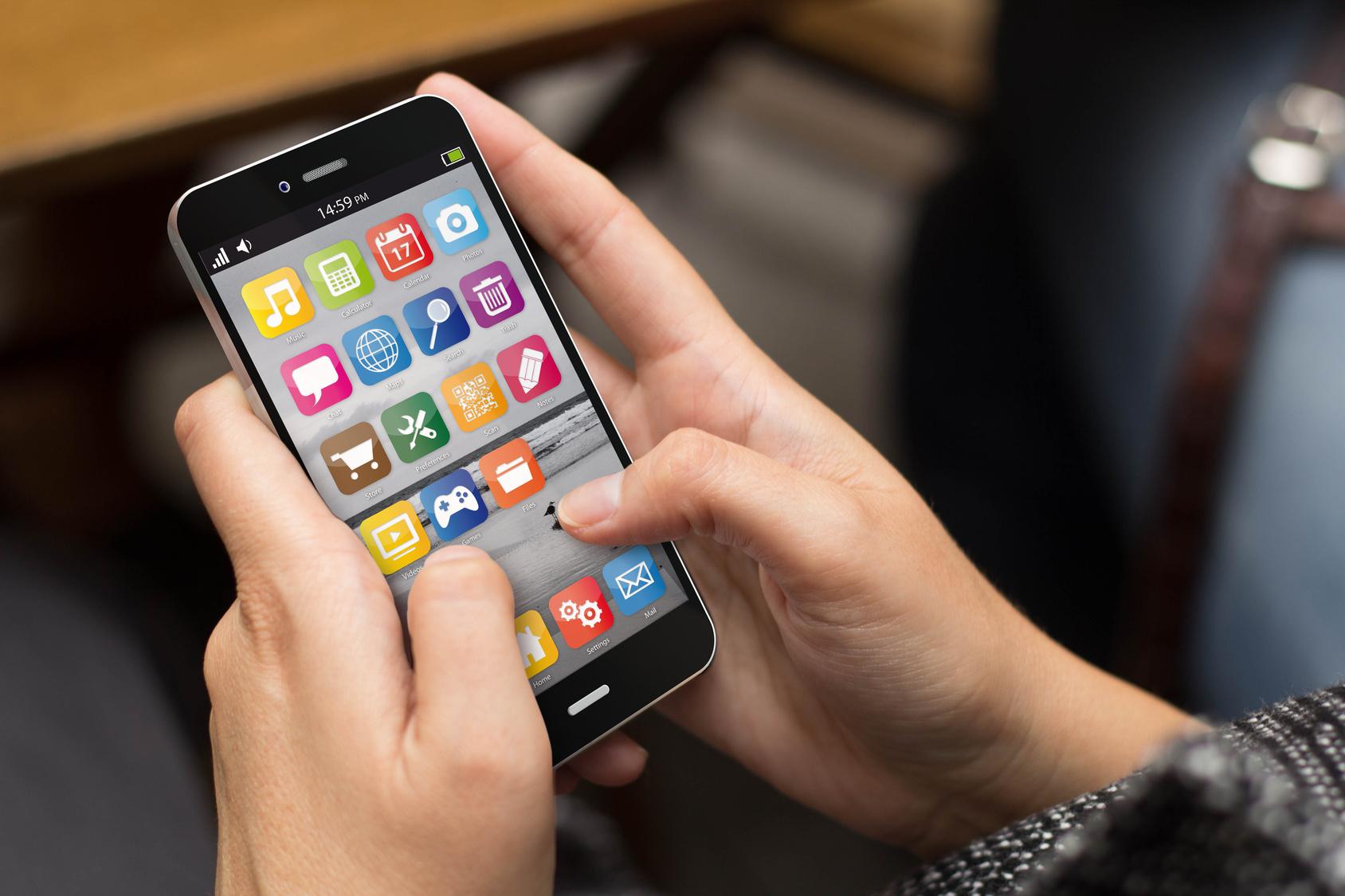 Gehirnjogging: Jemand hält ein Smartphone zwischen den Händen. und tippt auf die Apps auf dem Display