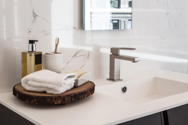 Hautpflege Tablett mit Handtuch, Stück- und Flüssigseife und Zahnbürste stehen auf dem Waschbecken