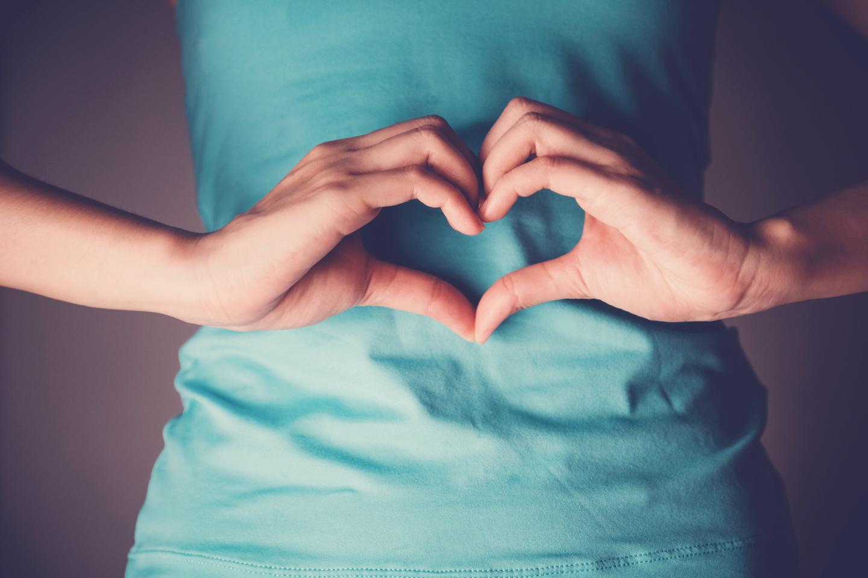 Frau formt mit Händen ein Herz vor ihrem Bauch, gesunde Darmflora