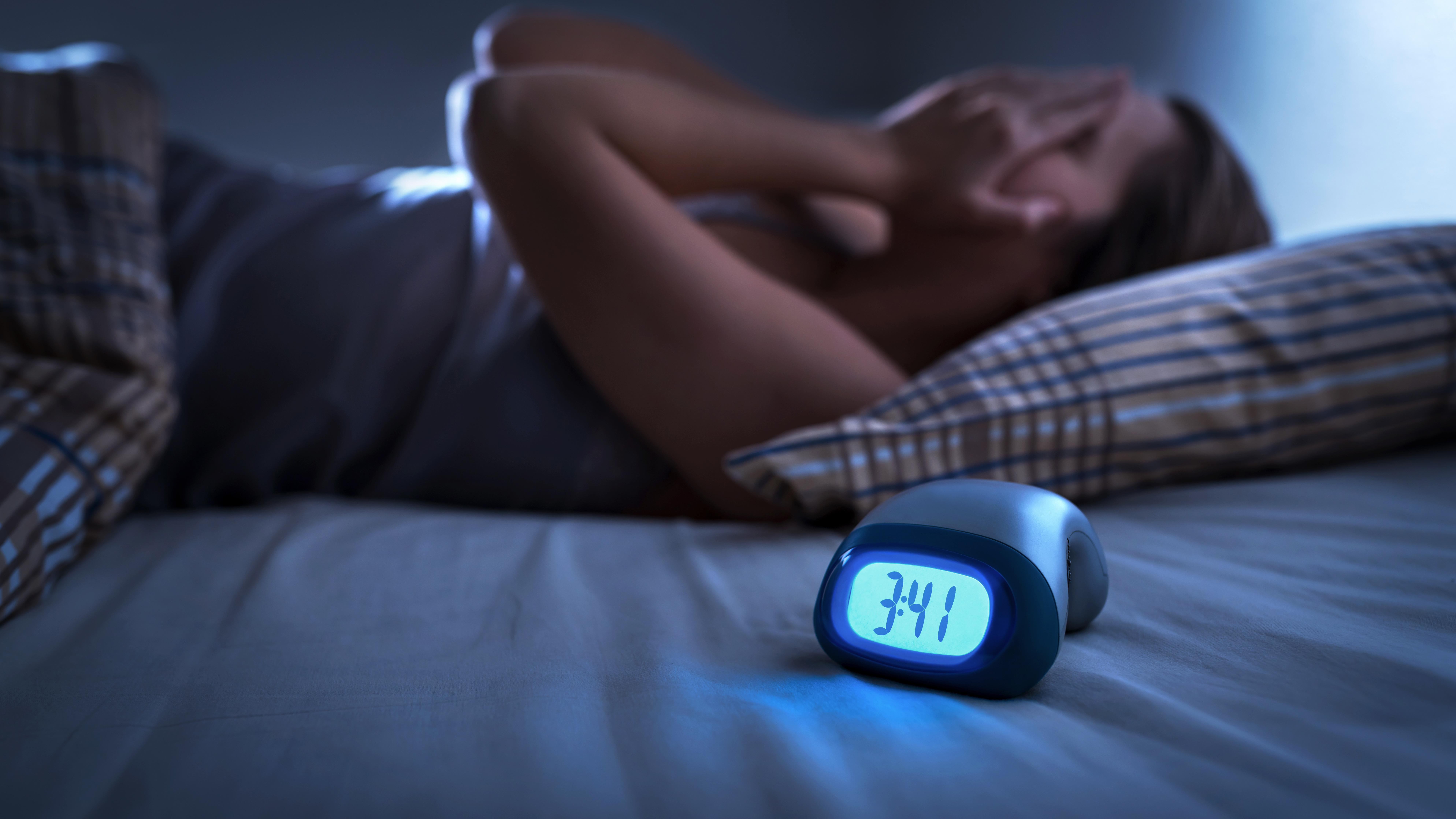 Schlaflose Frau hält Hände vor Gesicht. Wecker steht auf dem Bett