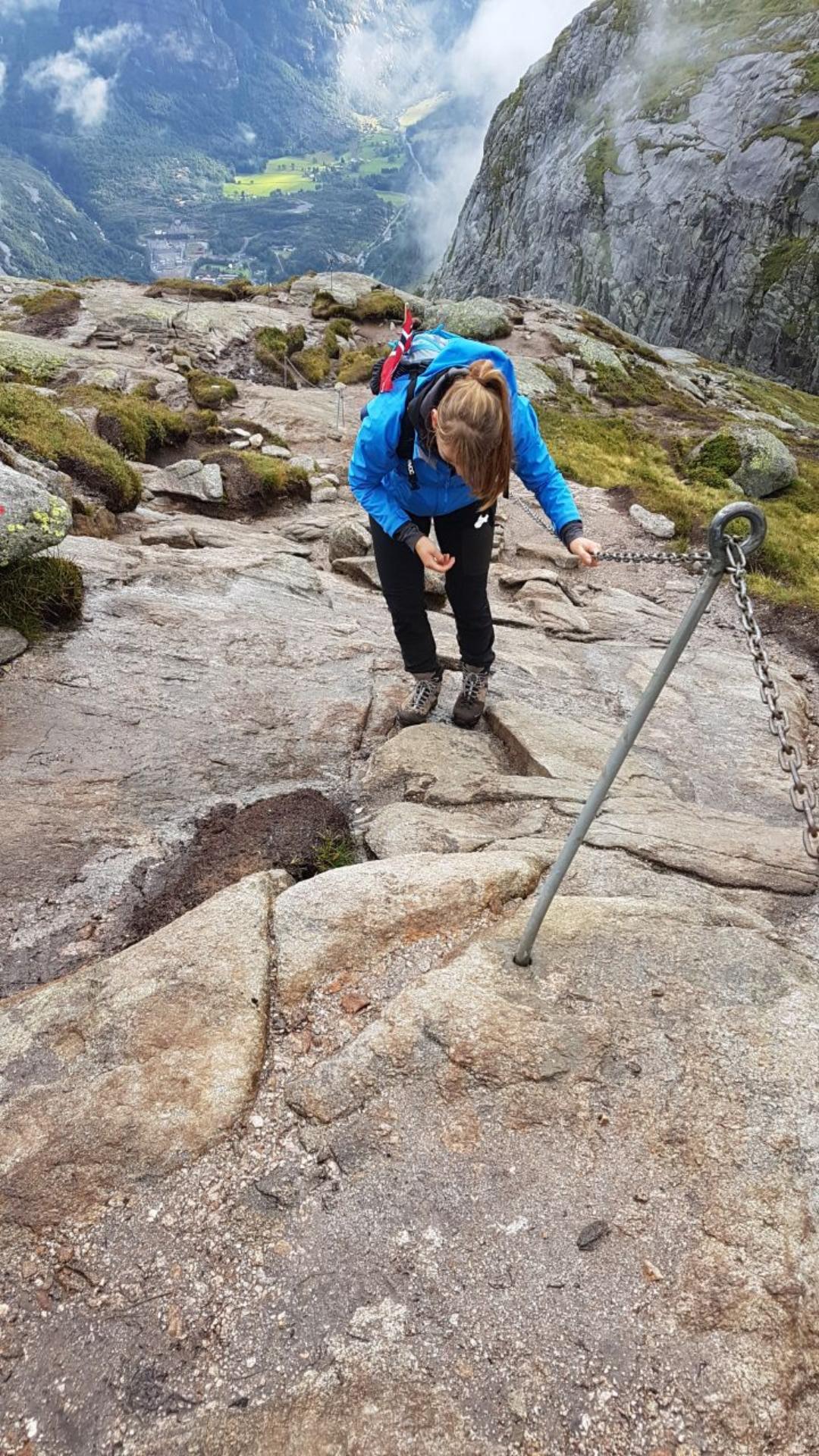 Monika klettert die Felswand am Stahlseil auf dem Weg zum Kjeragbolten hoch