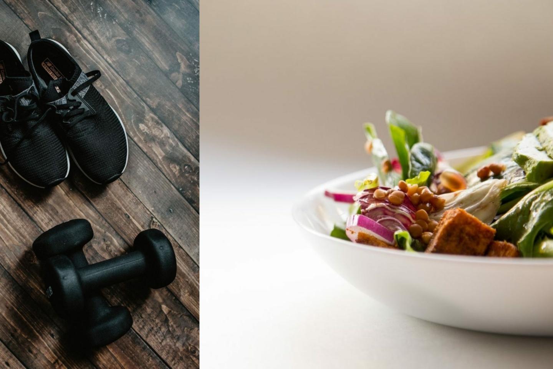 Schwarze Sportschuhe und Hanteln auf einem Holzboden und eine Schale mit Salat und Gemüse