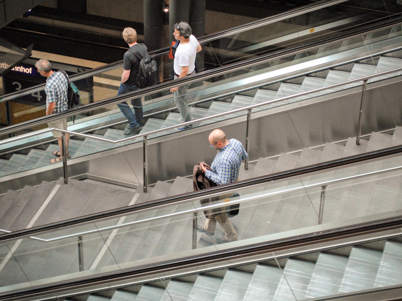 Auf die Treppe, fertig, los: Ein Mann geht zwischen zwei Rolltreppen die Treppe herunter, während drei andere Rolltreppe fahren