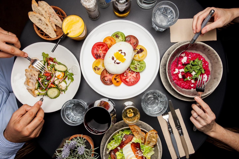 Ernährung: Mann und Frau sitzen am Tisch und haben verschiedene Speisen vor sich