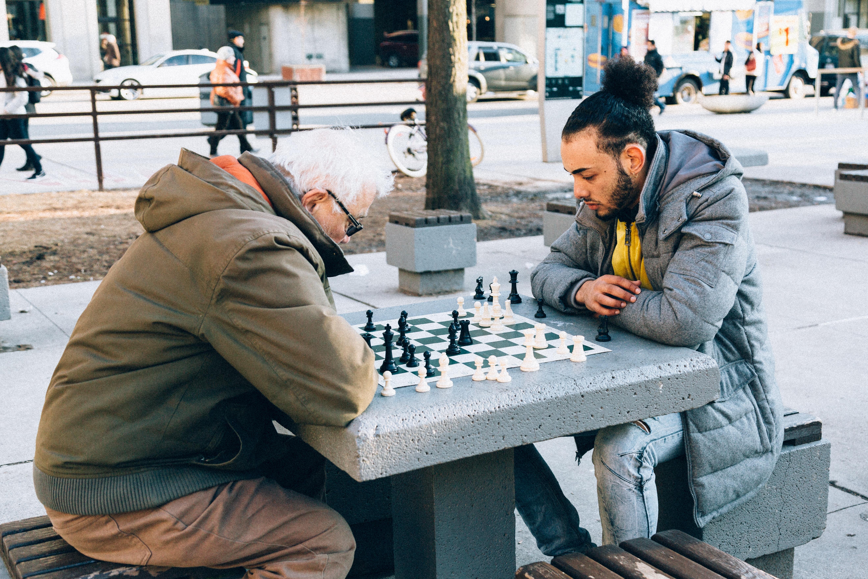 Ein älterer und jüngerer Mann spielen an einem Tisch auf dem Bürgersteig Schach