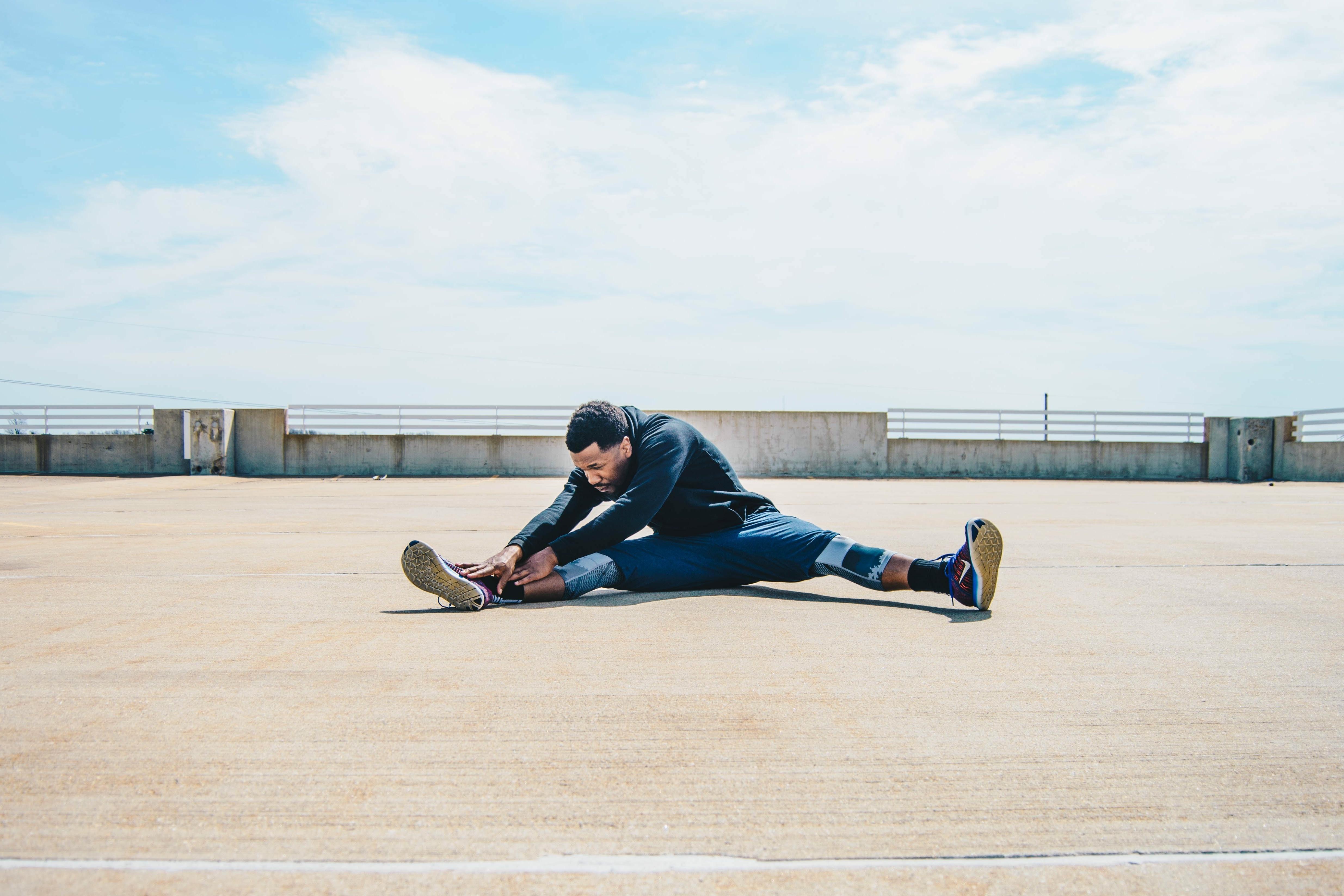 Outdoor-Sport: Mann stretcht sich im Sitzen auf einem Flachdach.