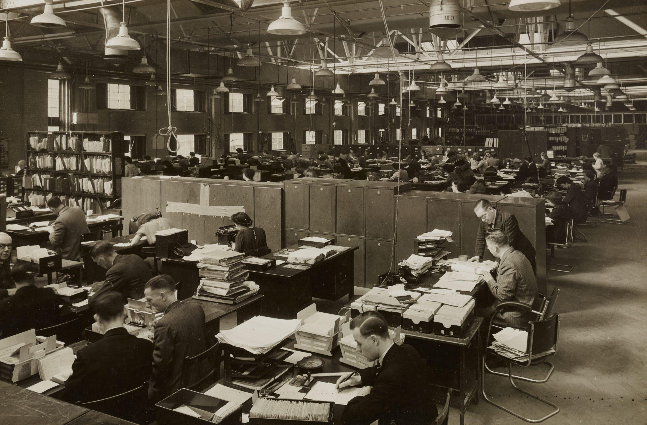 Frauen und Männer in einem Großraumbüro um 1940