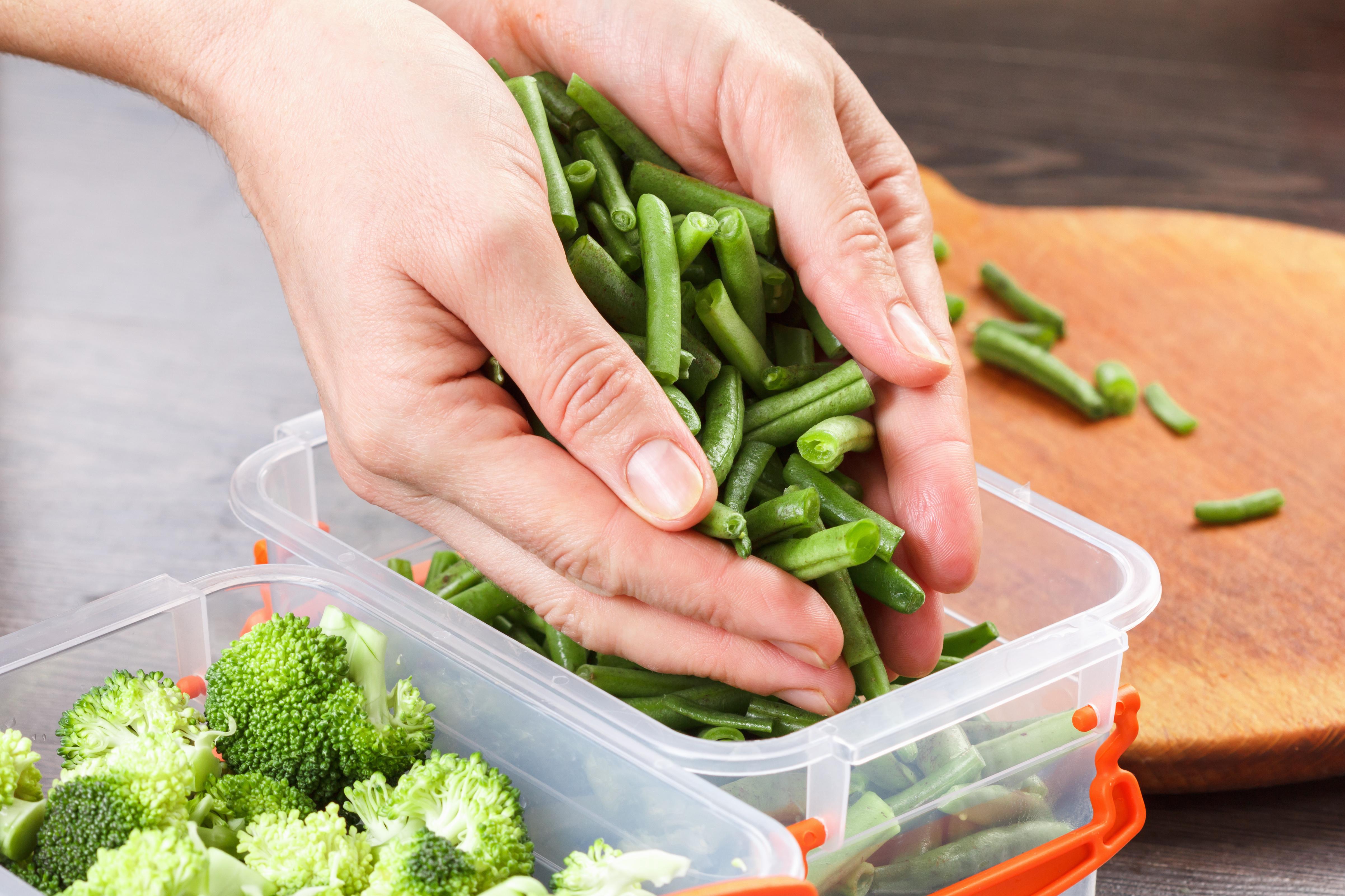 Klein geschnittene Bohnen werden in eine Gefrierbox per Hand gefüllt. Eine Box mit Brokkoli steht daneben