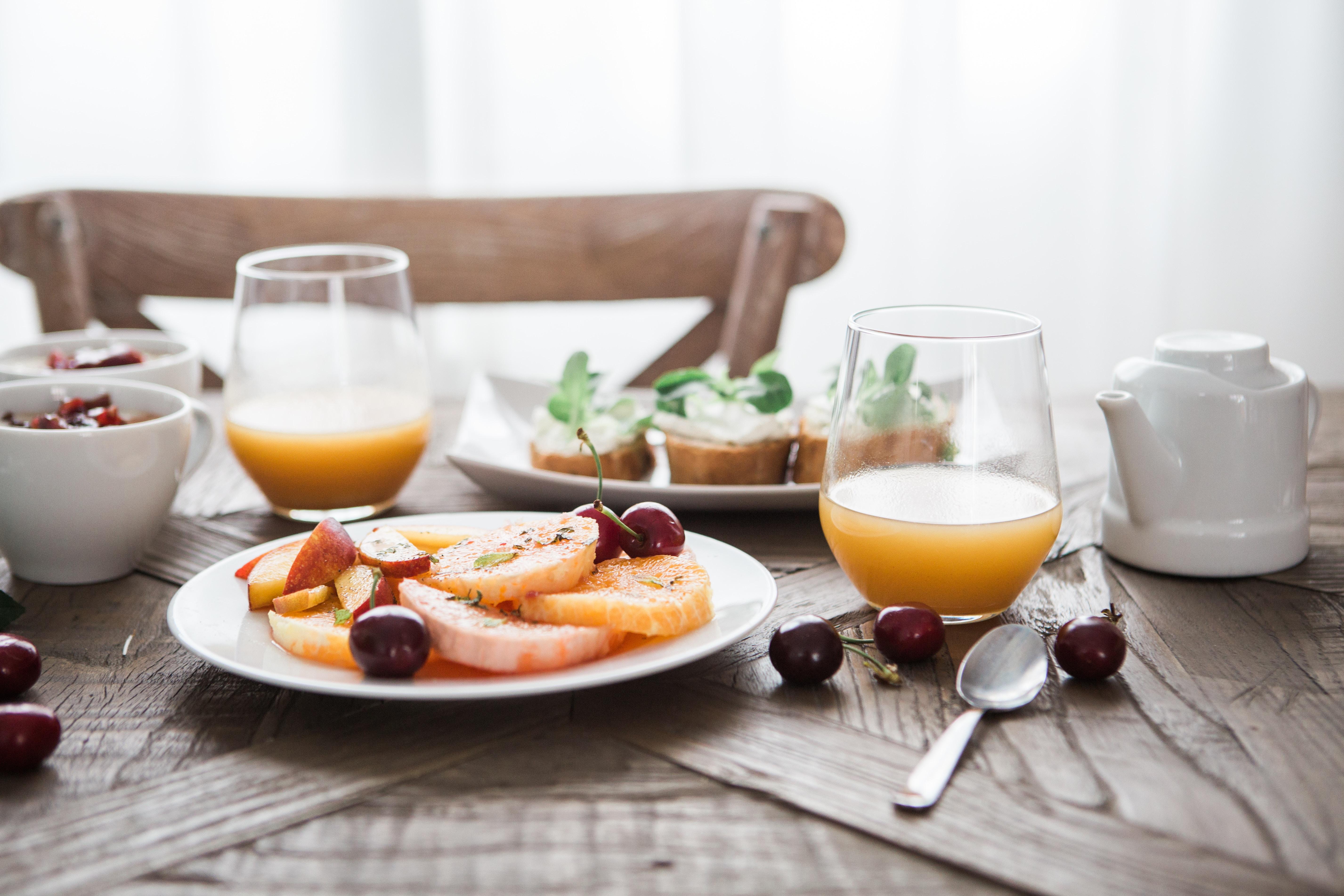 Hautpflege: Dazu gehört auch ausgewogene Ernährung. Obst, Saft und Quarkbrote stehen auf einem Holztisch