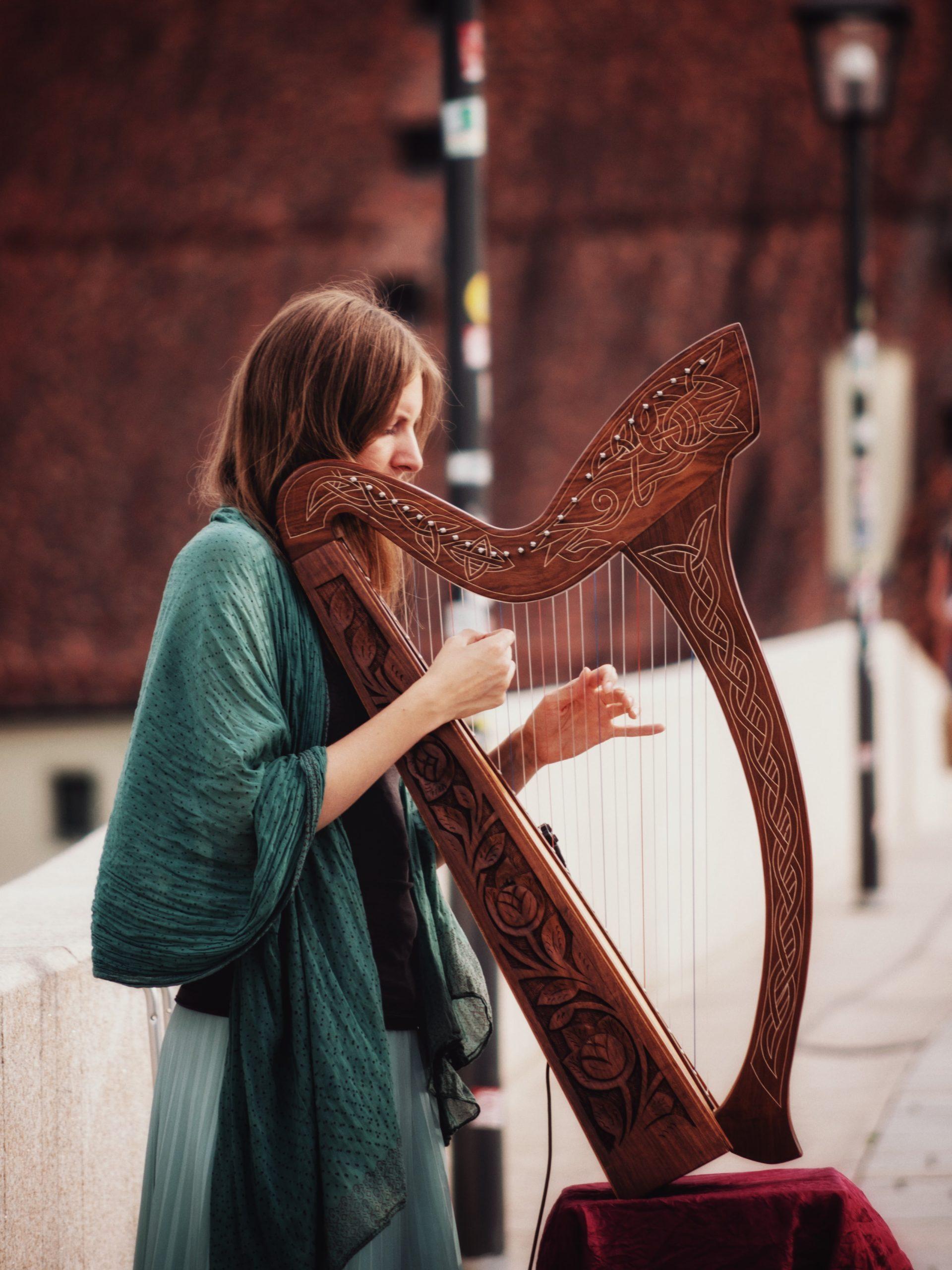 Irland: Eine Frau in grünem Gewand spielt auf eine irischen Harfe