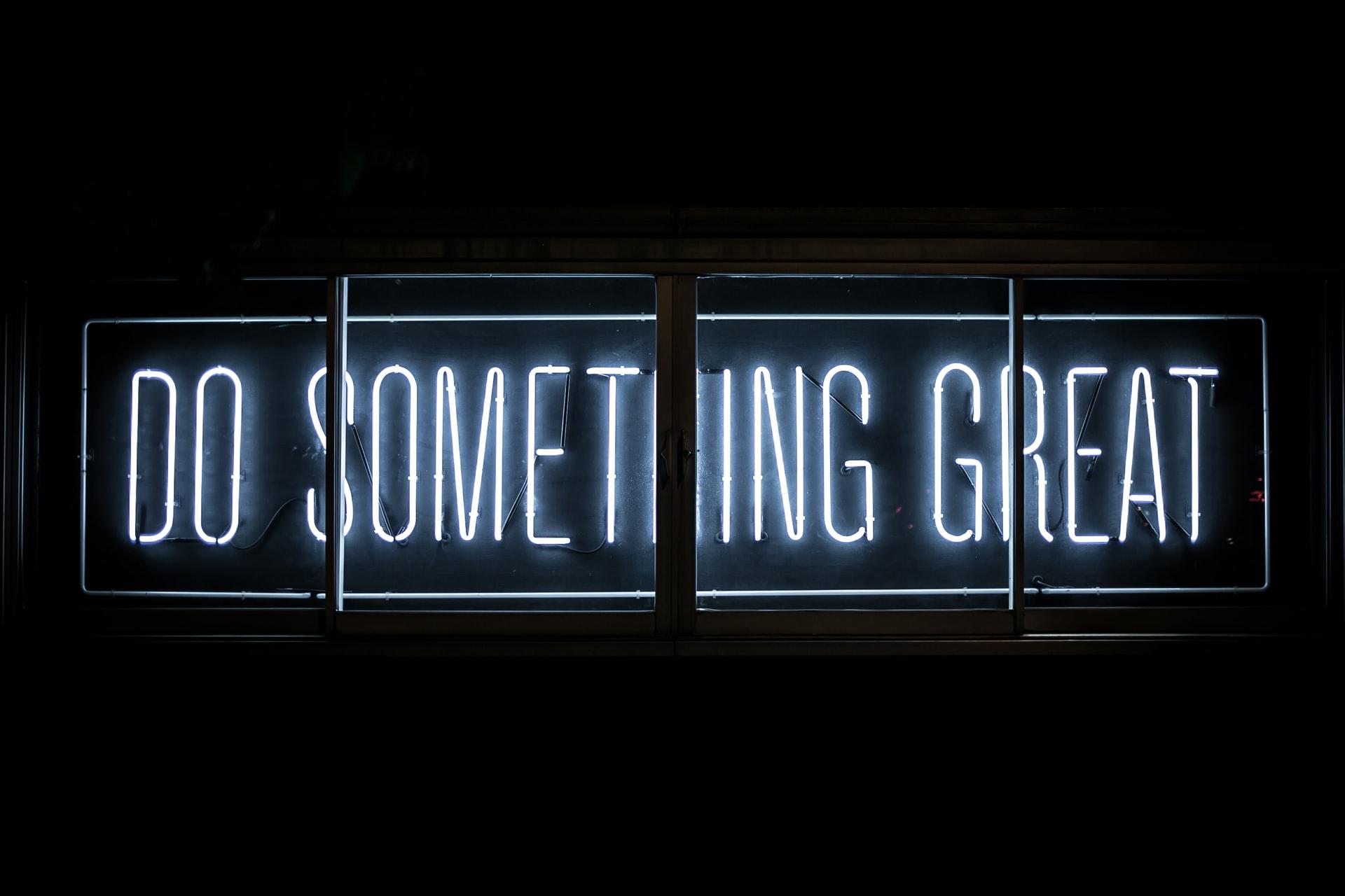 Neonschild mit Schriftzug Do Something Great hinter einem Fenster