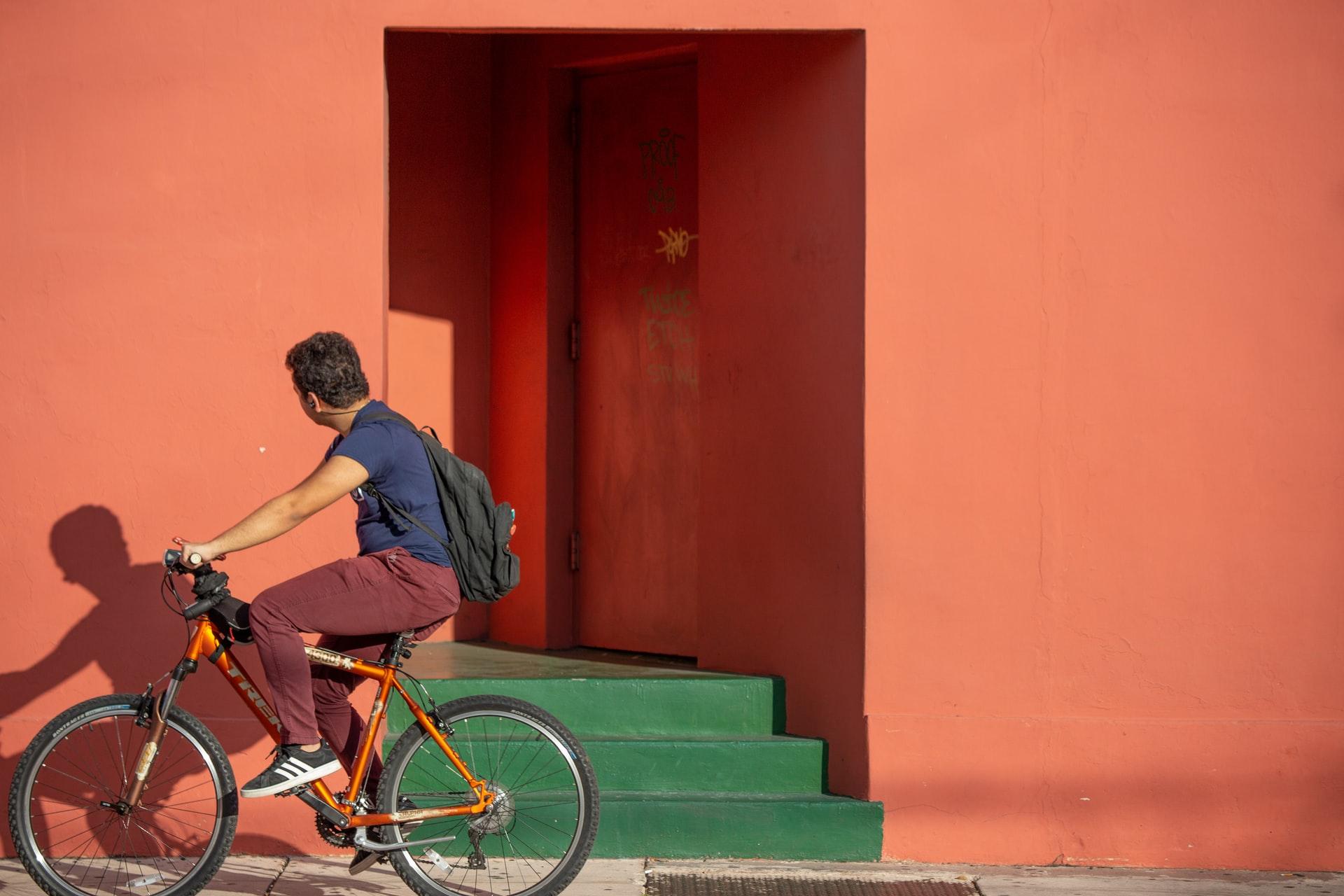 Mann auf ein Fahrrad fährt an einer orangenen Wand entlang