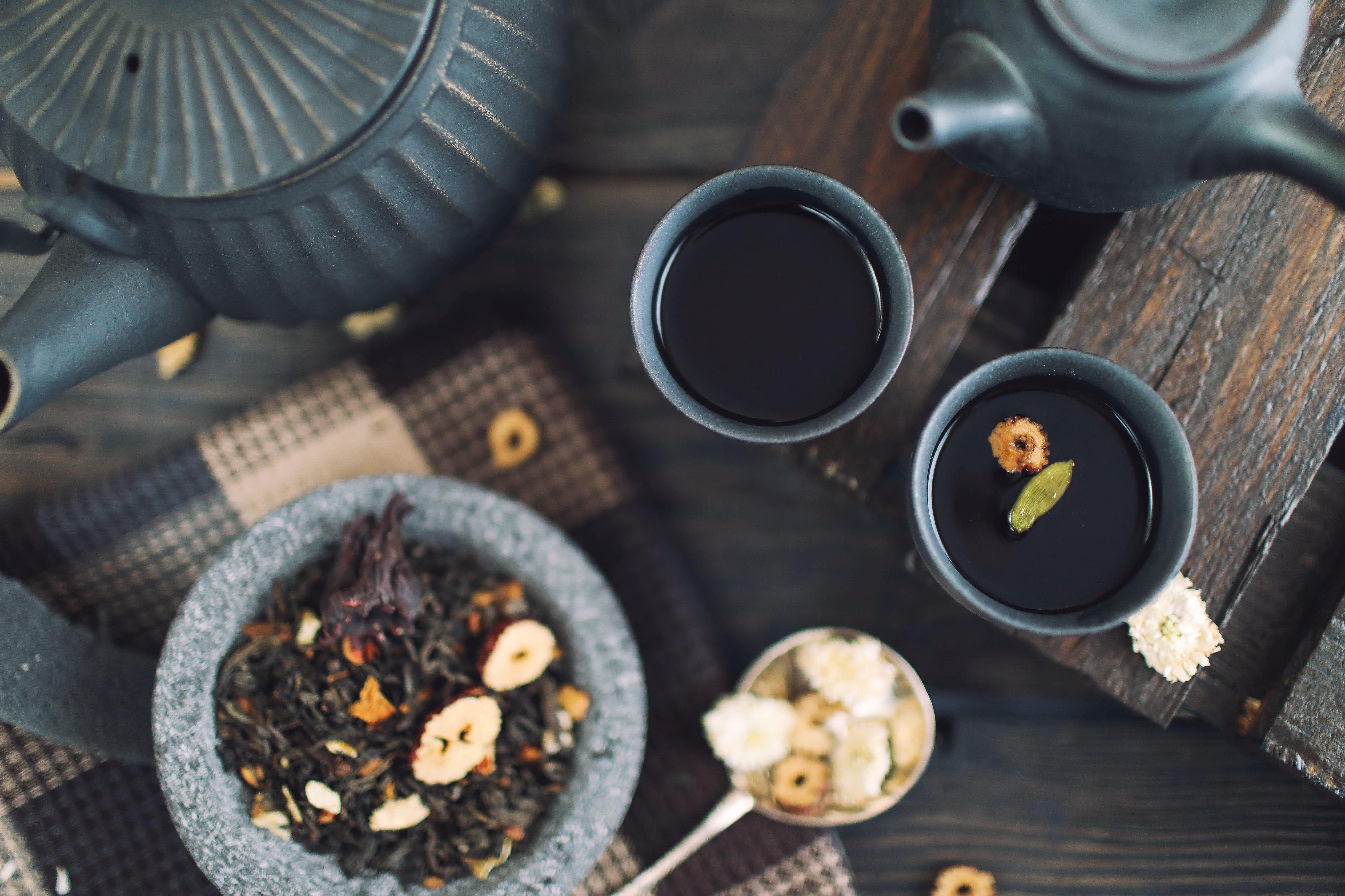 Kräutertee: lose Kräuter neben zwei Teetassen und -kanne.