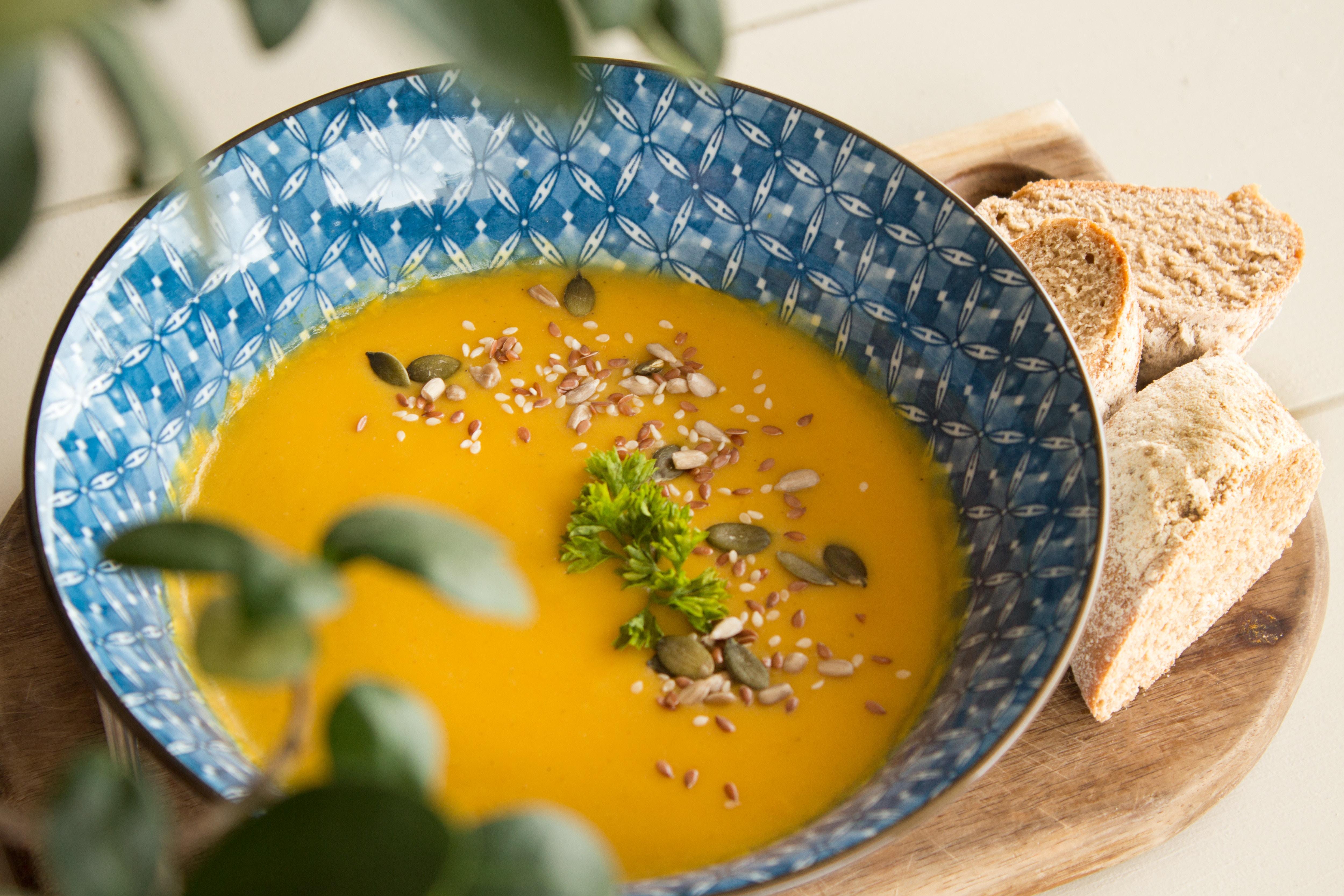 Suppen: Suppe aus Kürbis in einer blau-gemusterten Schüssel auf einem Holzbrett mit Brot.
