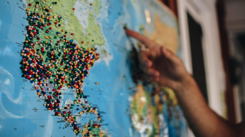 Reiseblogs mit Fernwehgarantie: Eine Weltkarte ist voller farbiger Stecknadeln auf, die ein Mann mit seinem Finger zeigt